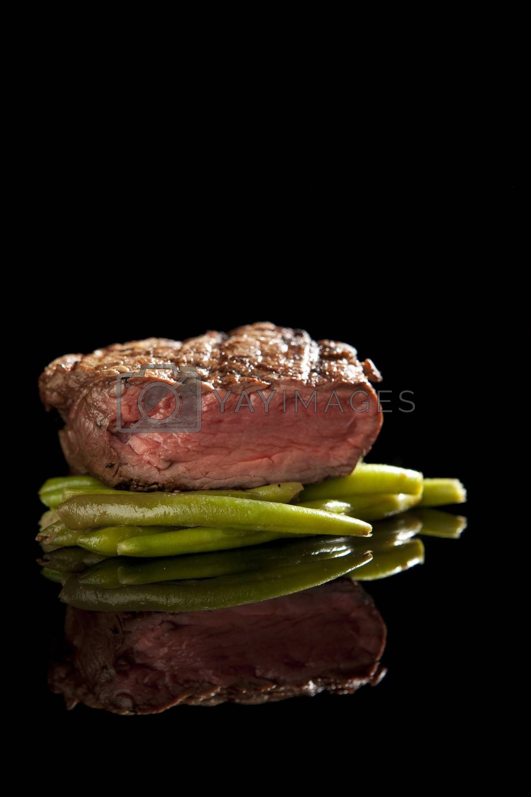 beef steak on black background with beans.