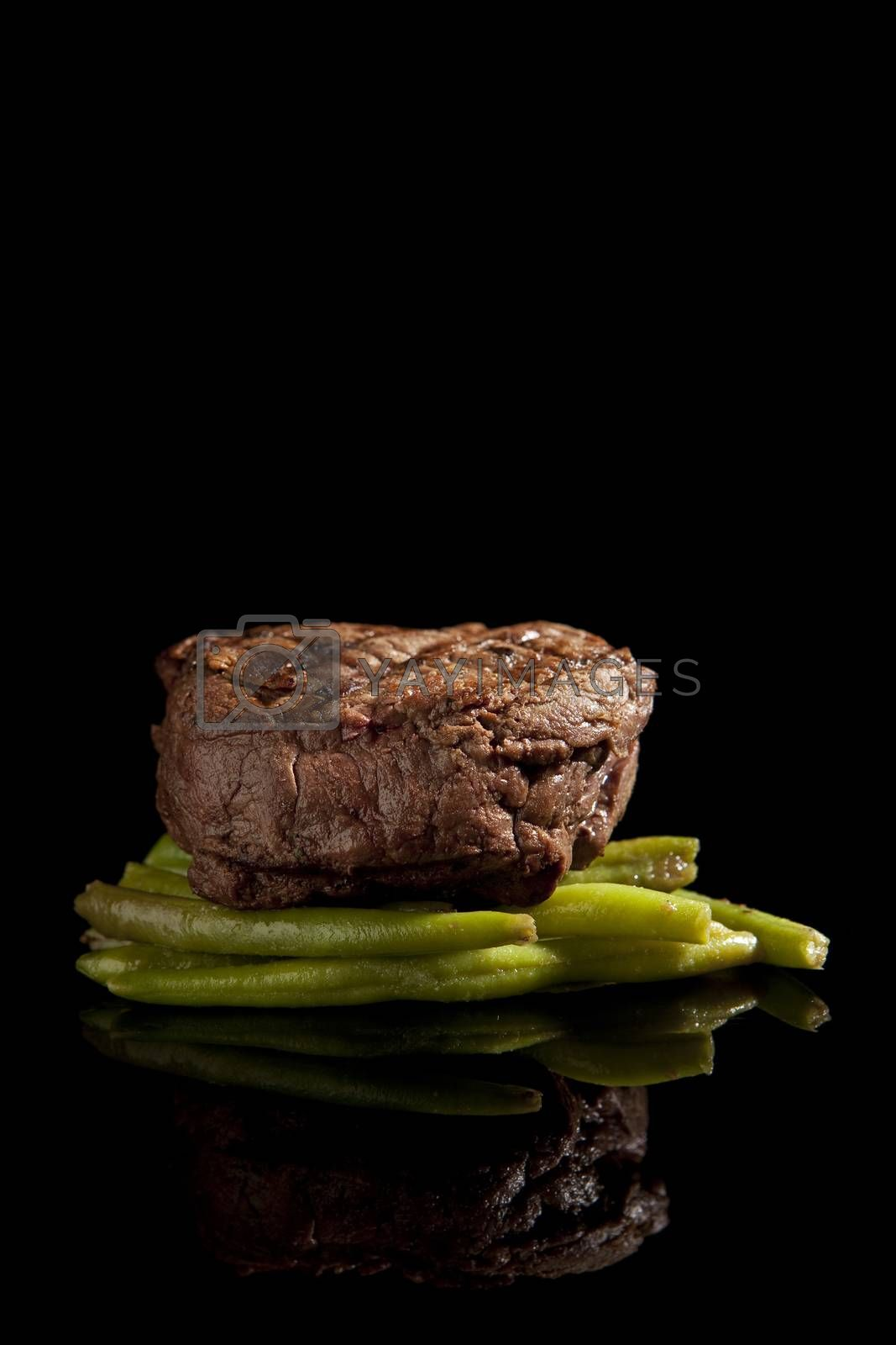 beef steak with beans on black background