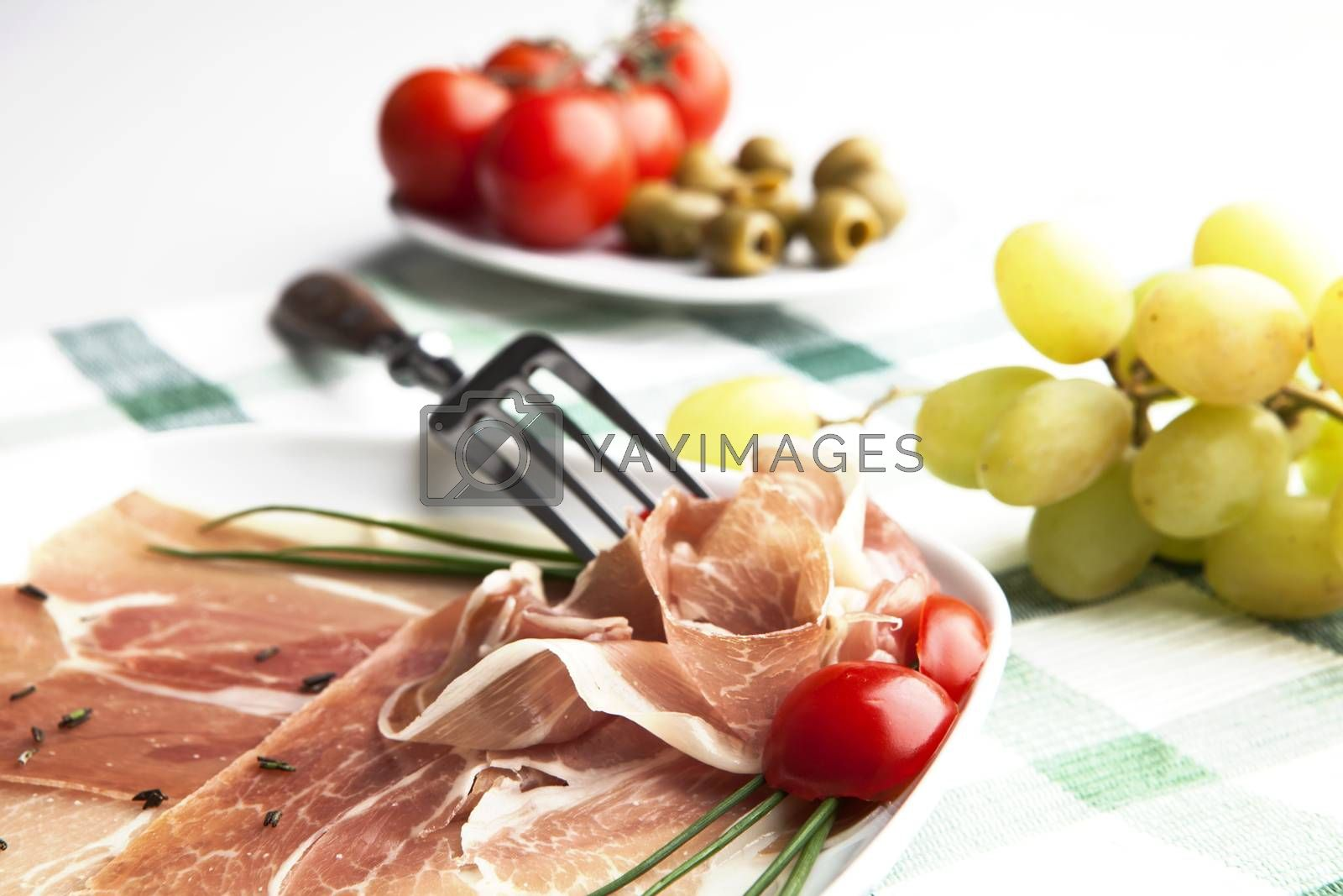 Delicious prosciutto plate with olives, tomatos and grapes.