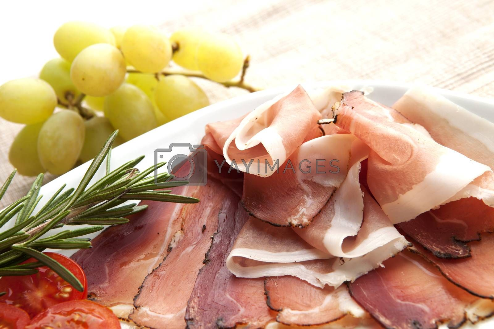 Delicious prosciutto plate with tomatos, grapes and rosemary.