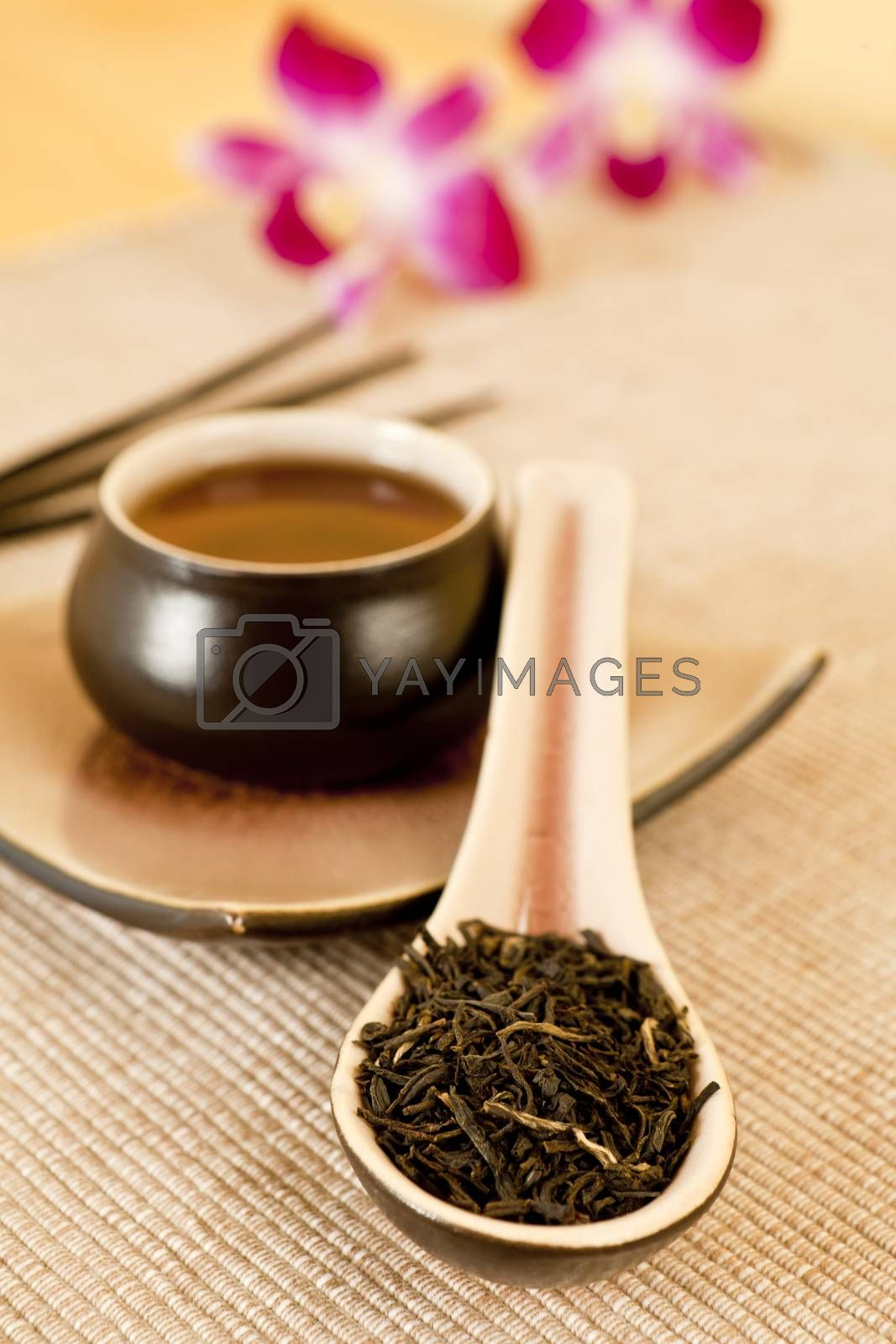 Tea leaves o a tea spoon, cup of black tea, insence sticks and flowers in background