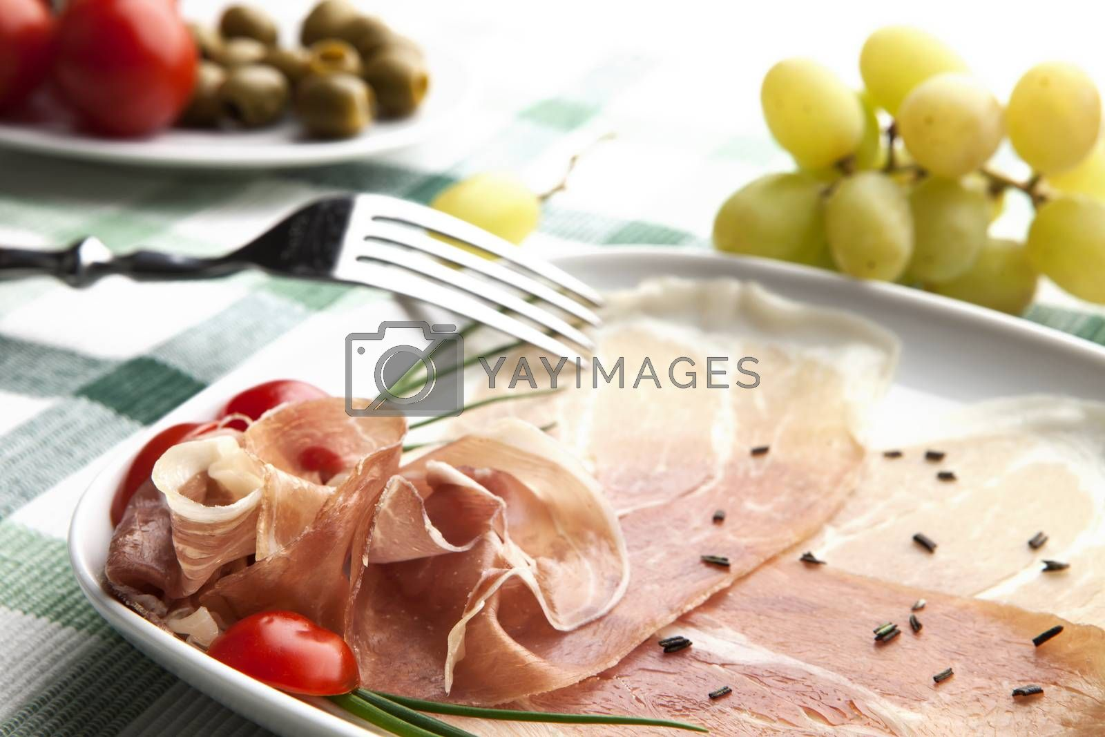 Delicious prosciutto plate with olives, tomatos, grapes and a fork.