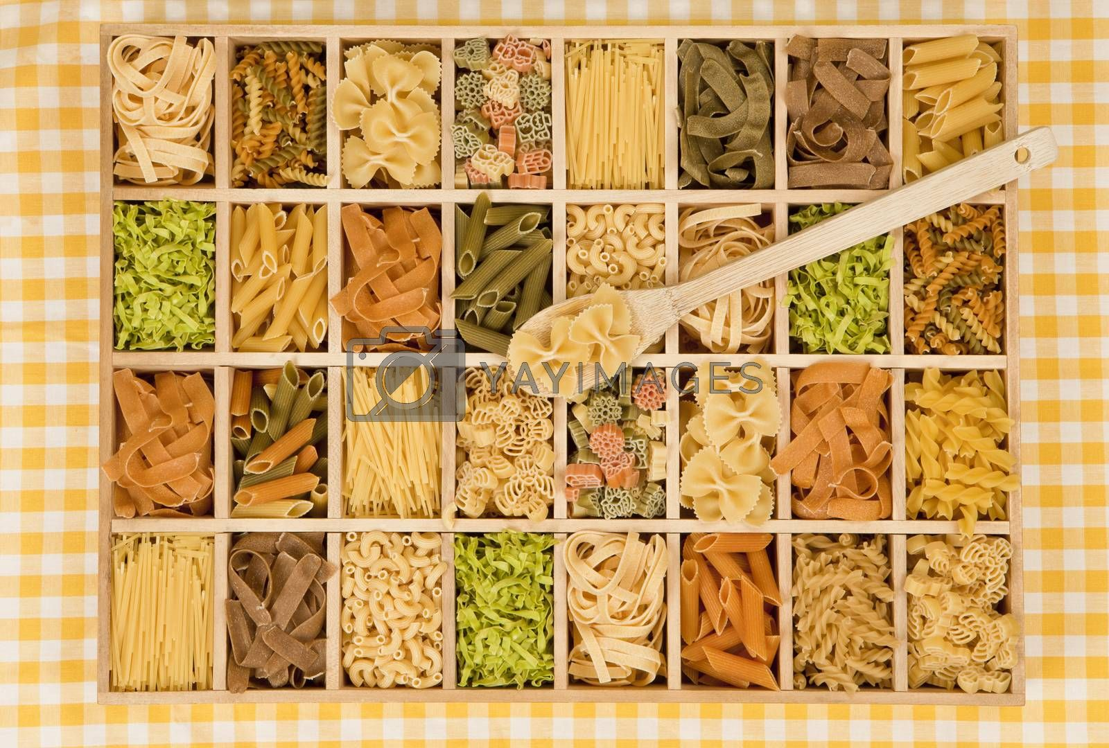 Different noodle sorts in wooden box with wooden spoon.