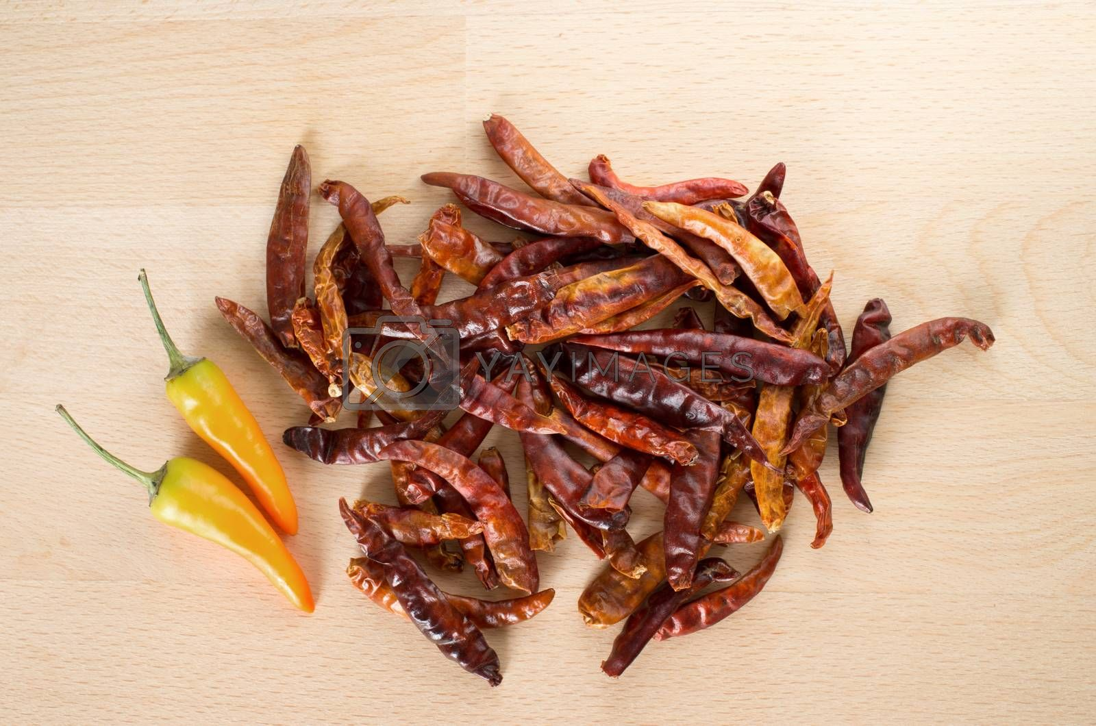 Dried red chili and yellow fresh chili on wooden cut board by daoleduc