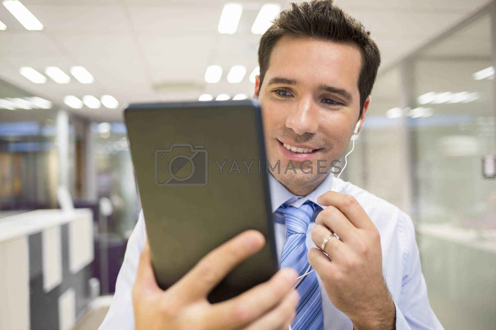 Smiling Businessman chatting on internet with Tablet Pc, office Background