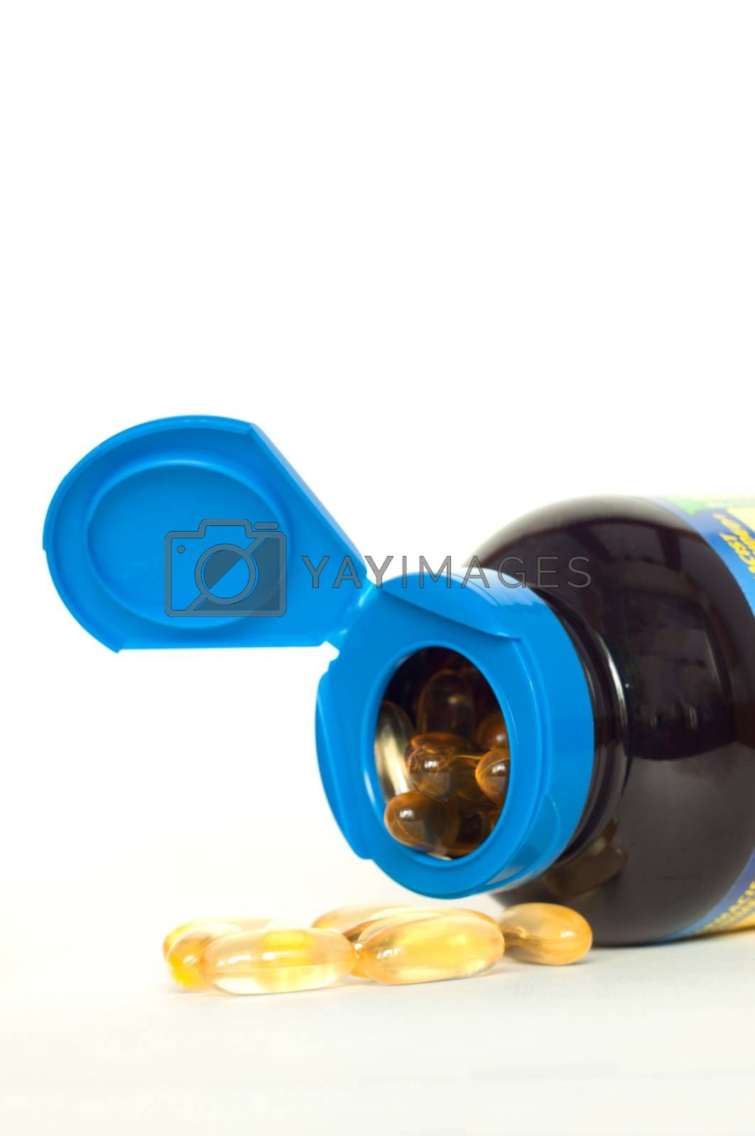 Open bottle of fish oil capsules on white background