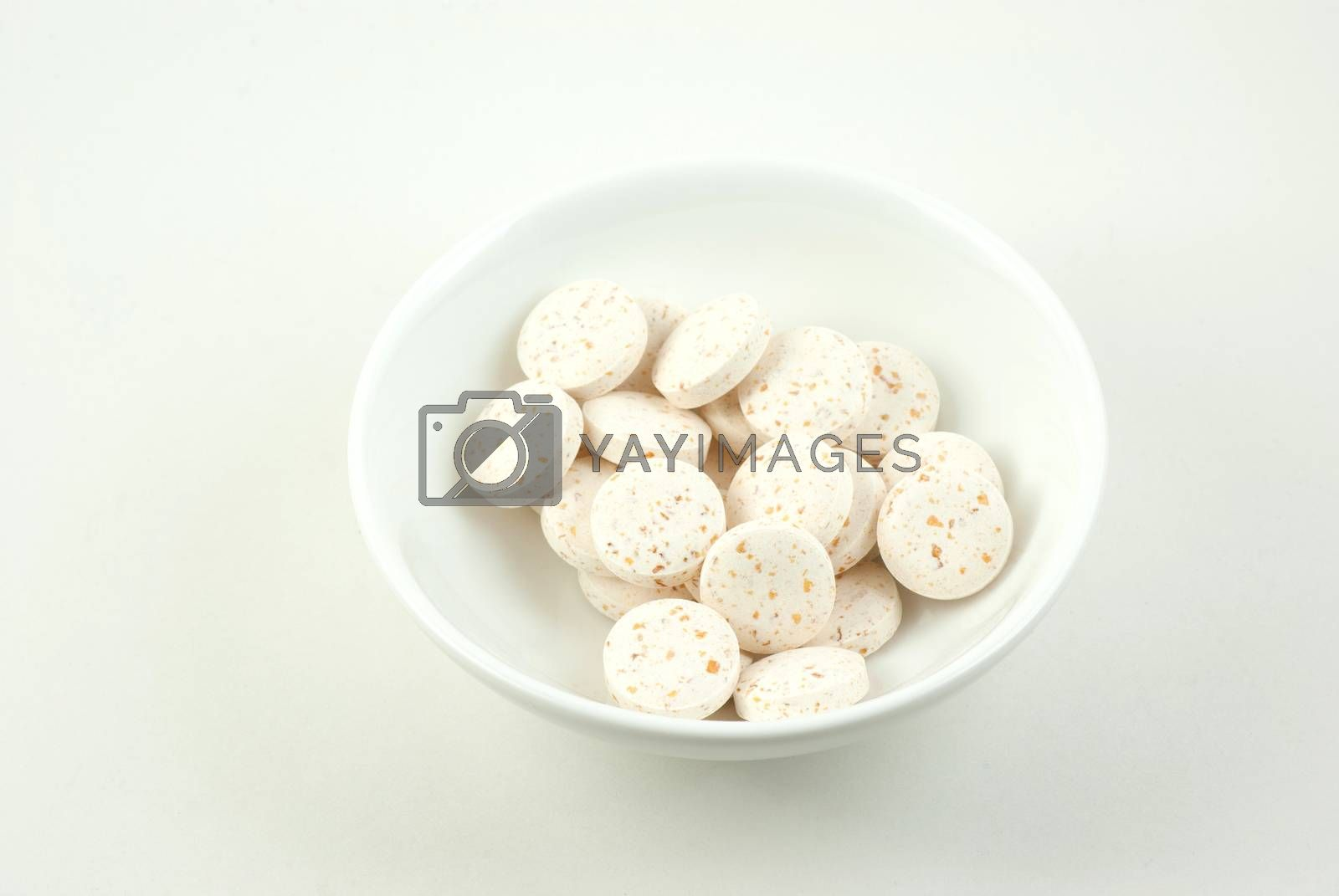 Small dish containing vitamin C pills
