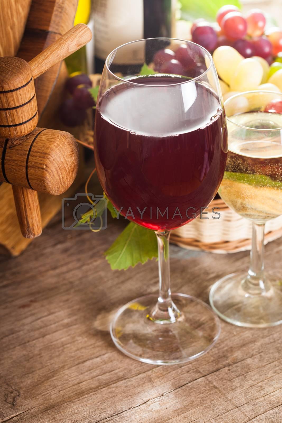 Glasses of wine on the old wooden background over oak barrel