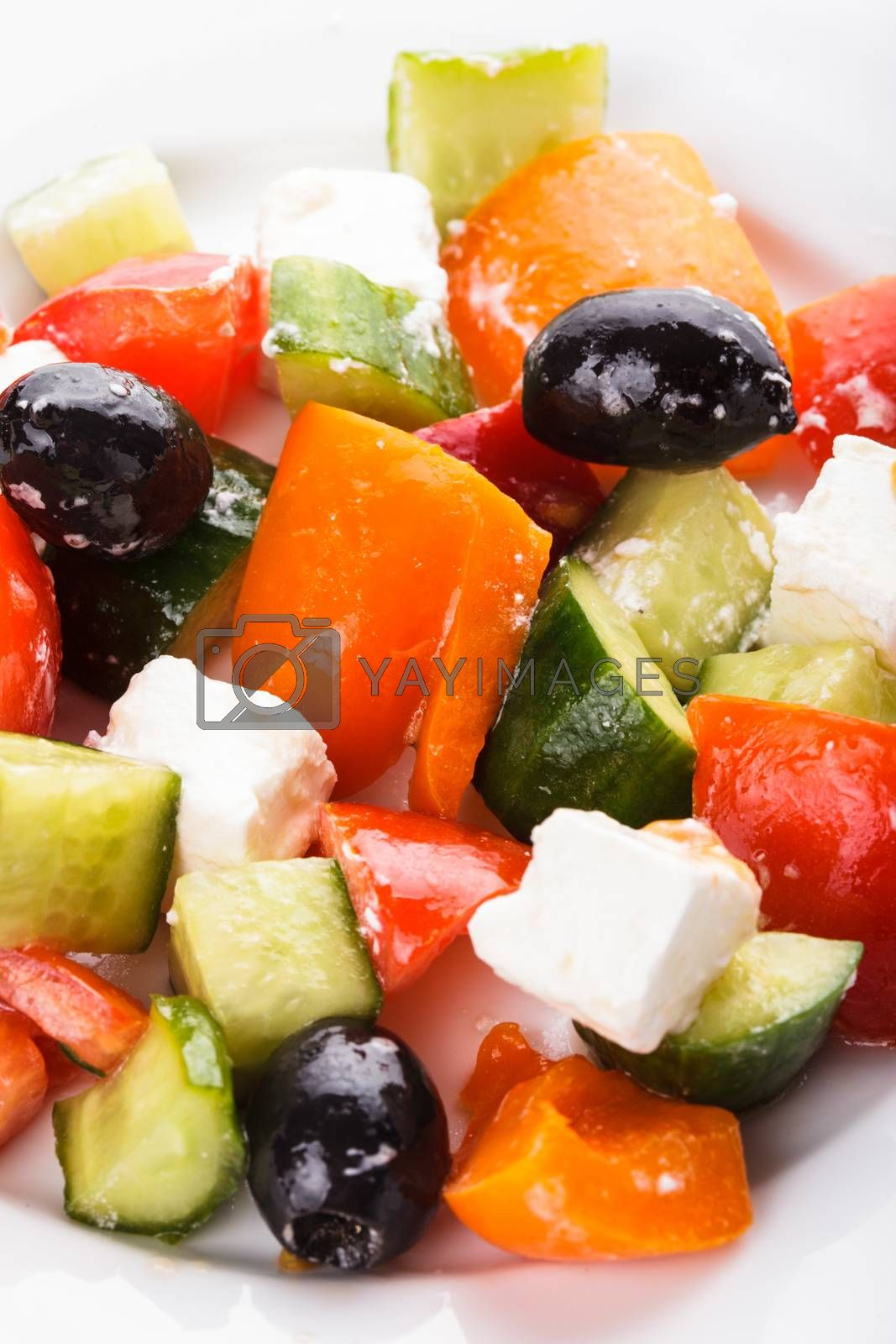 Greek salad with feta cheese macro on white plate