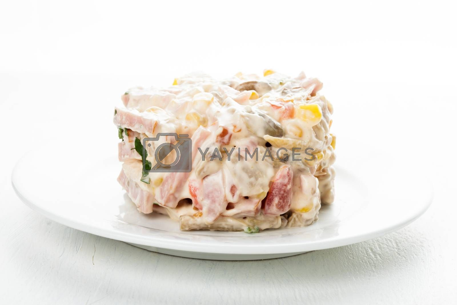 Portion of salad with ham, meat, mushrooms, vegetables and mayonnaise