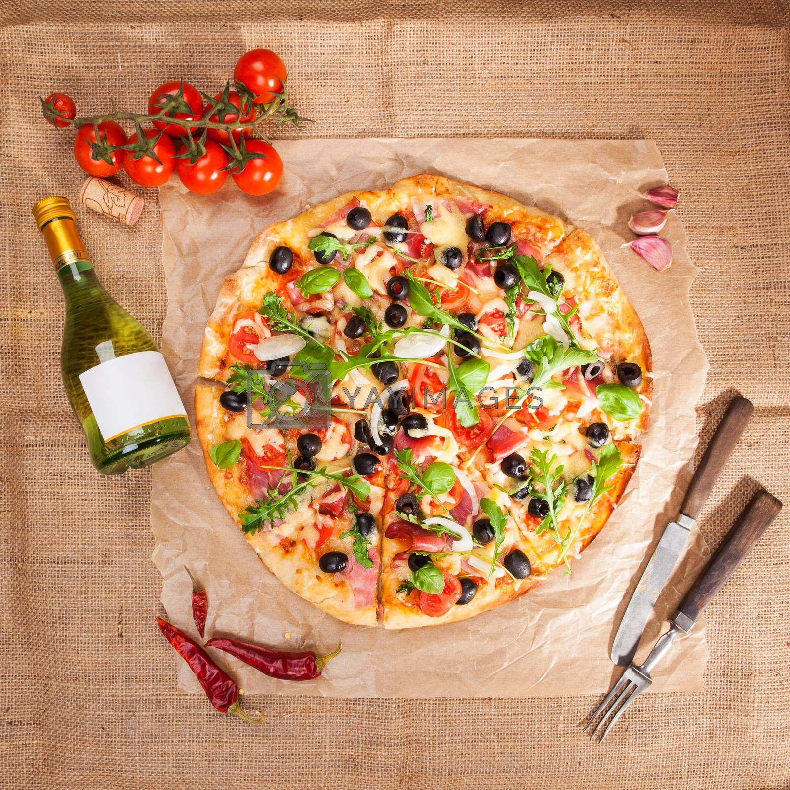 Delicious tasty pizza, fresh tomatoes, garlic, bottle of white wine and wooden cutlery on brown background, top view. Rustic country style italian eating concpept.
