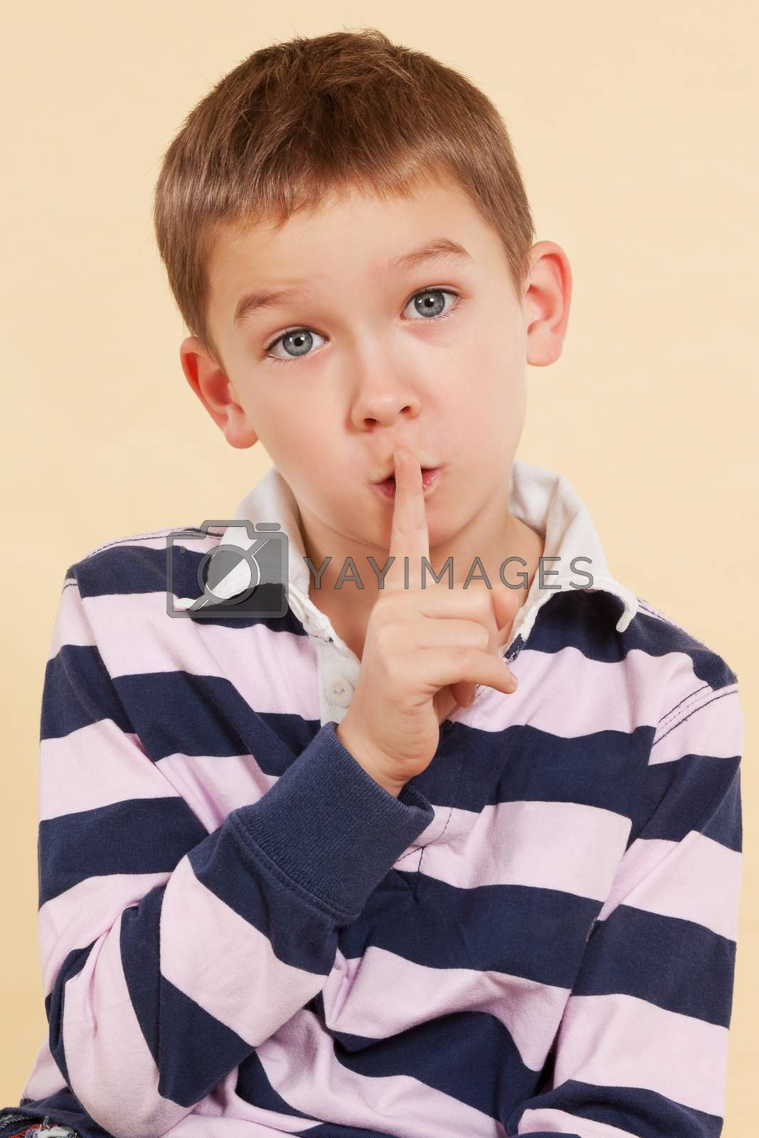 The secret.  Don't tell anyone. Young boy with finger over his mouth isolated on neutral background. Facial expressions concept. Psst