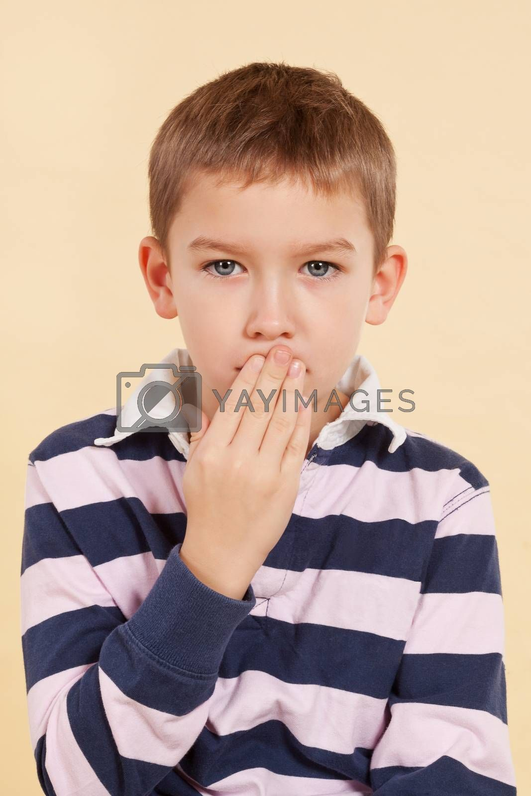 Young boy with black eye and hand over his mouth isolated. Domestic violence concept. Don't tell anyone. Psst
