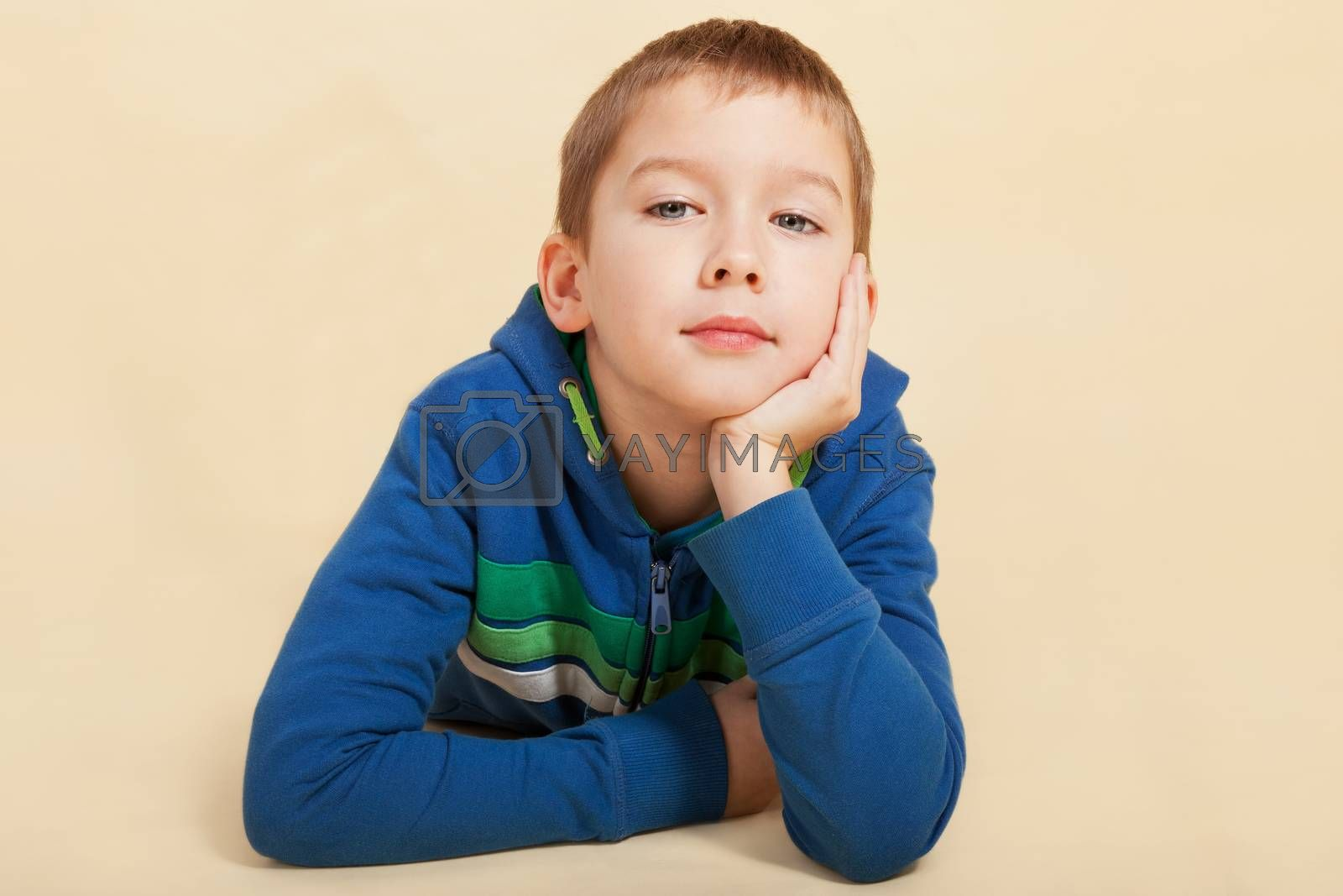 Young boy lying on the ground, looking into the camera with a smile and thinking. Youth concept