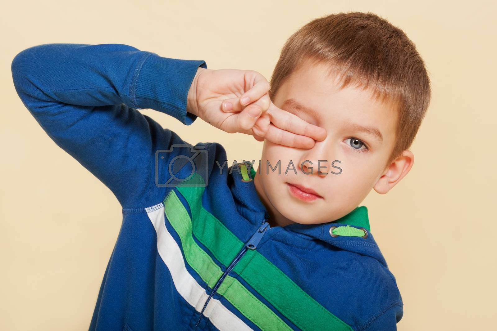 Young cute boy ten years old covering his eye and looking into the camera isolated. Youth fashion concept.