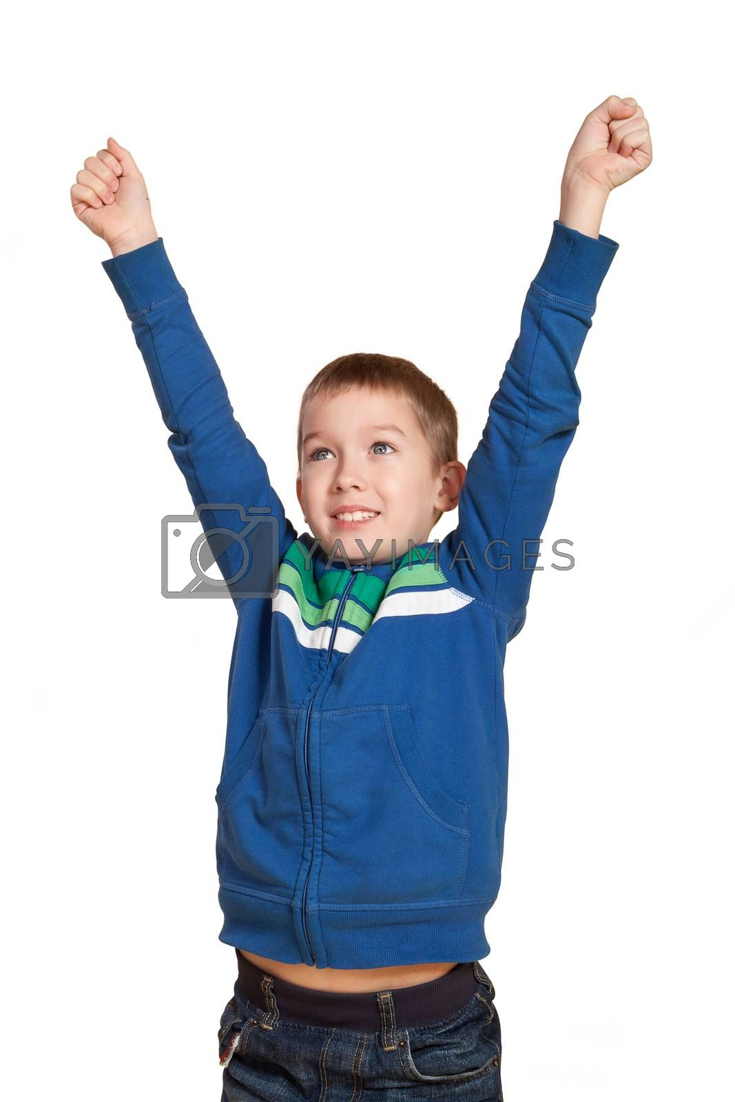 Young cute 10 year old white boy with hands in the air smiling expressing joy and victory. Expressions concept.