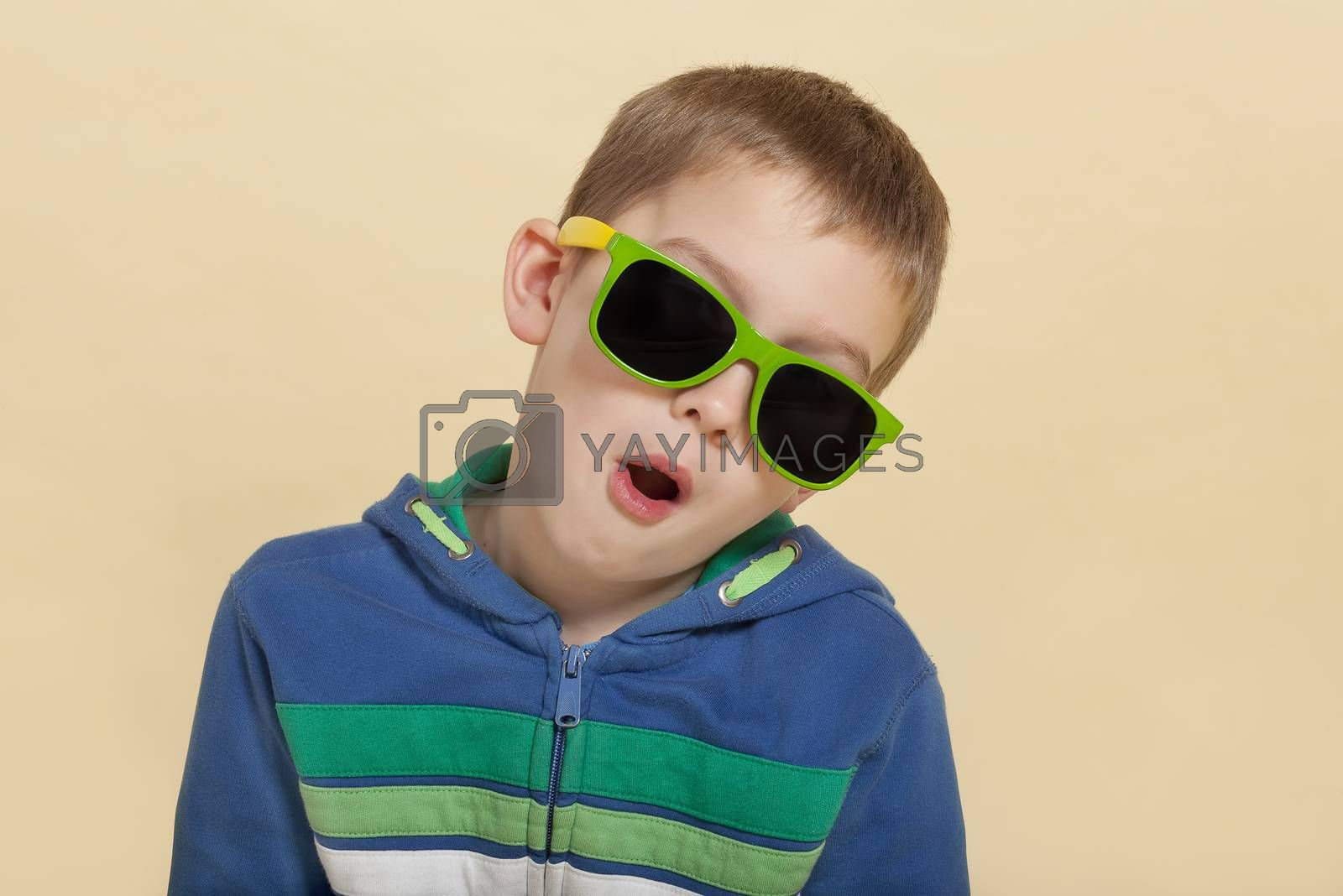 Funky cool young surprised boy with open mouth and yellow and green sunglasses. Youth fashion concept.