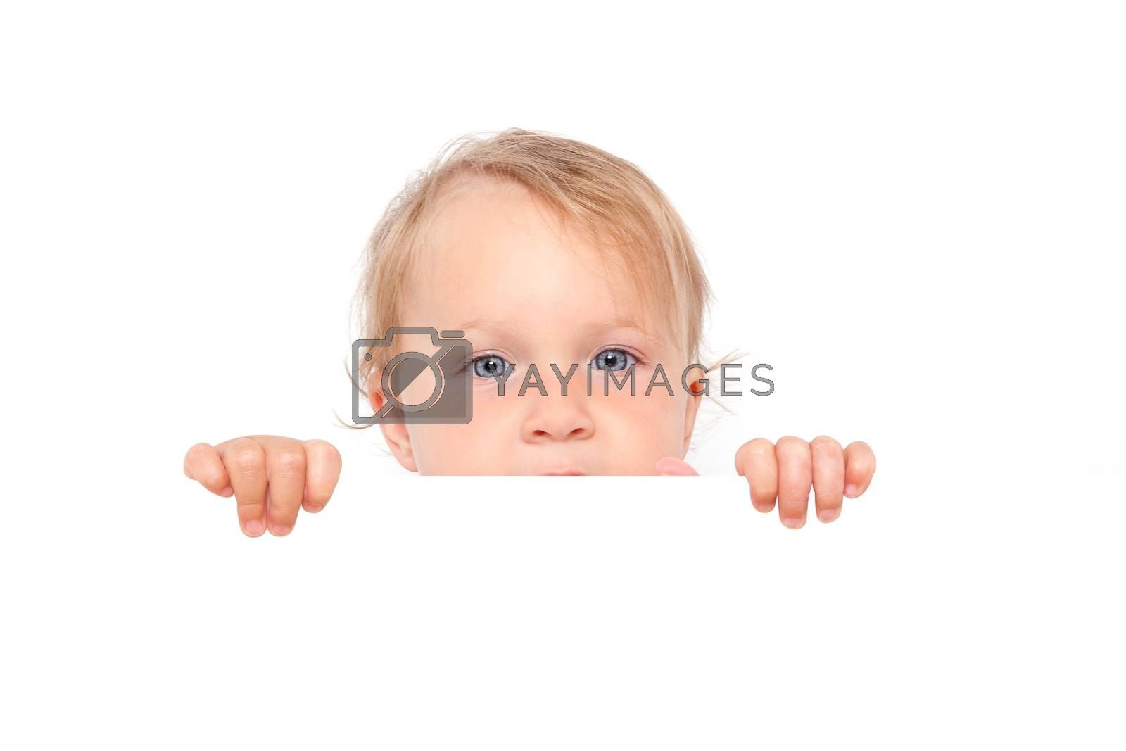 Cute blonde baby girl with big blue eyes looking over white board isolated on white background. Cute curious baby and family concept.