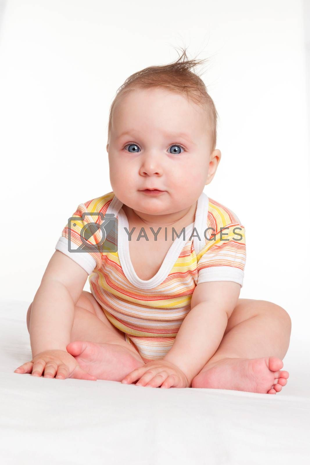 Cute caucasian baby girl sitting and looking into the camera isolated on white background.