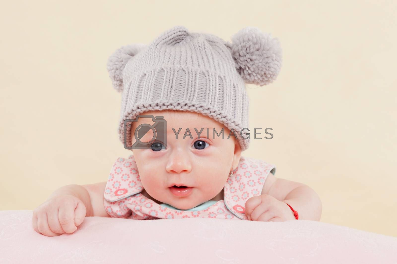 Beautiful cute surprised baby girl with grey cap lying on blanket faced into the camera.