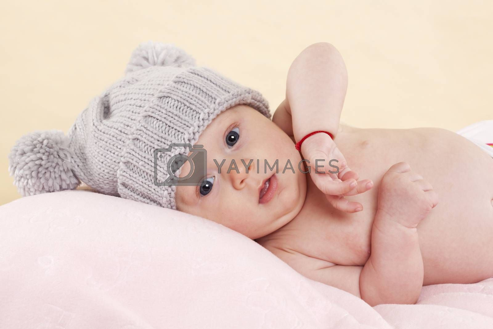 Cute naked baby girl with grey hat lying on a blanket and looking into the camera. Beautiful newborn concept.