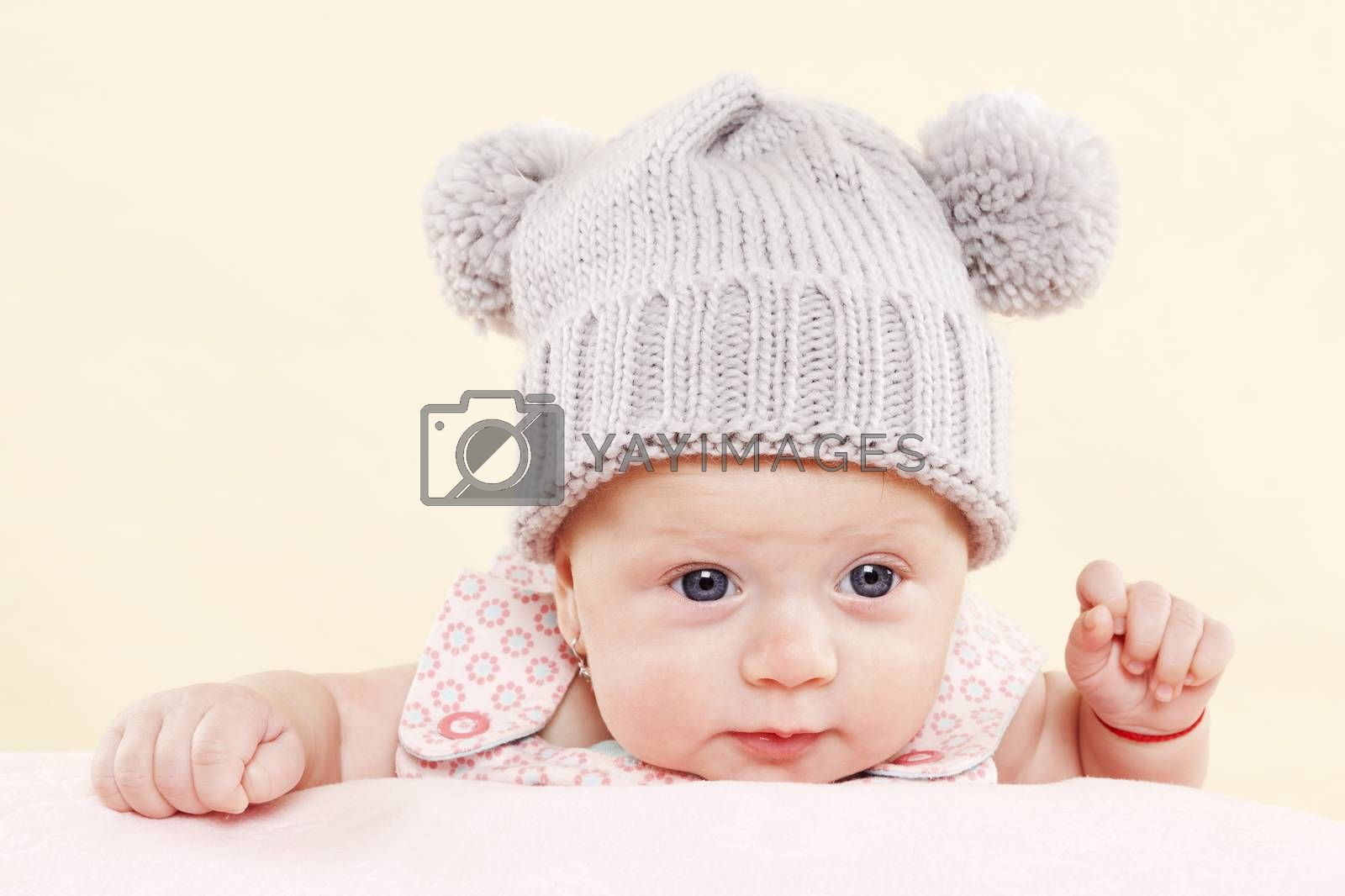 Cute baby girl with grey hat and blue eyes looking into the camera. Newborn baby concept.