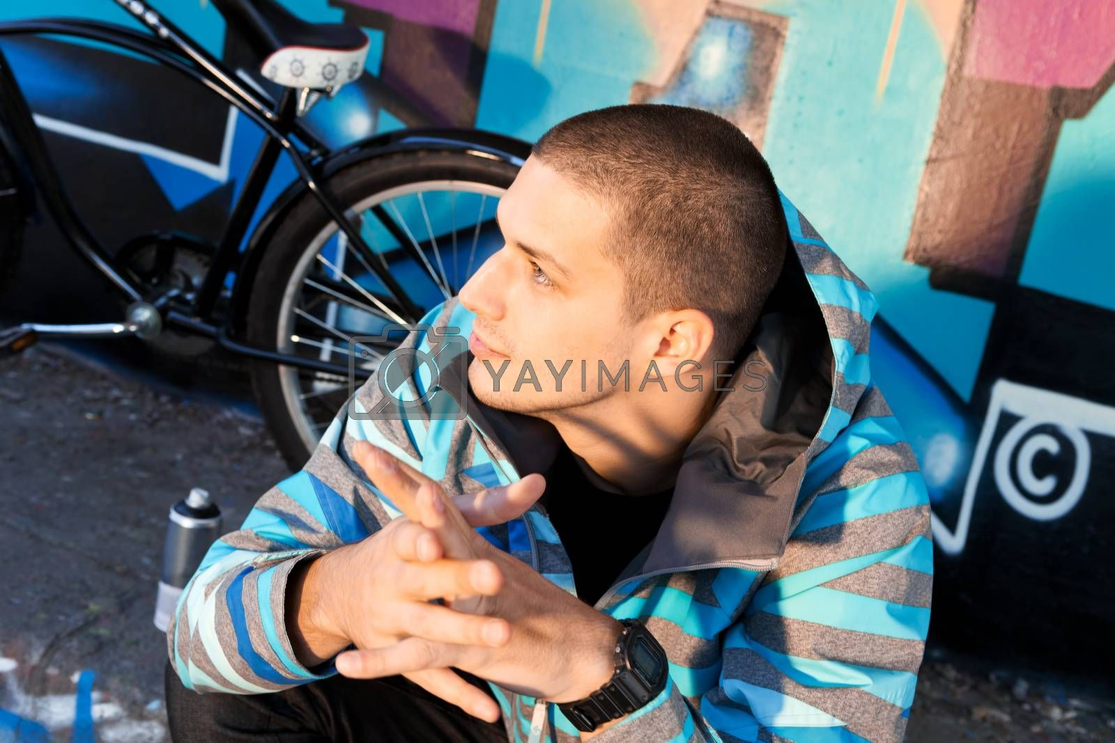 Young male graffiti artist sitting in front of finished piece on wall with city cruiser bike leaning next to him. Urban culture.
