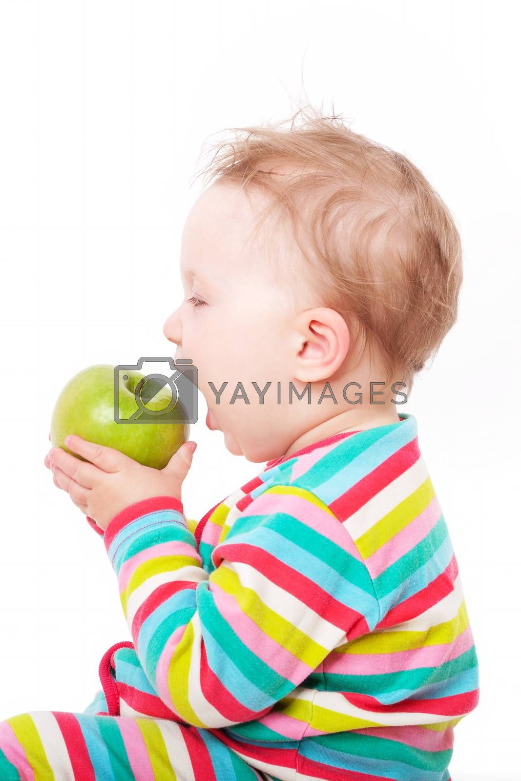 Small cute baby girl in colorful clothing holding and eating green apple isolated on white background. First teeth concept.