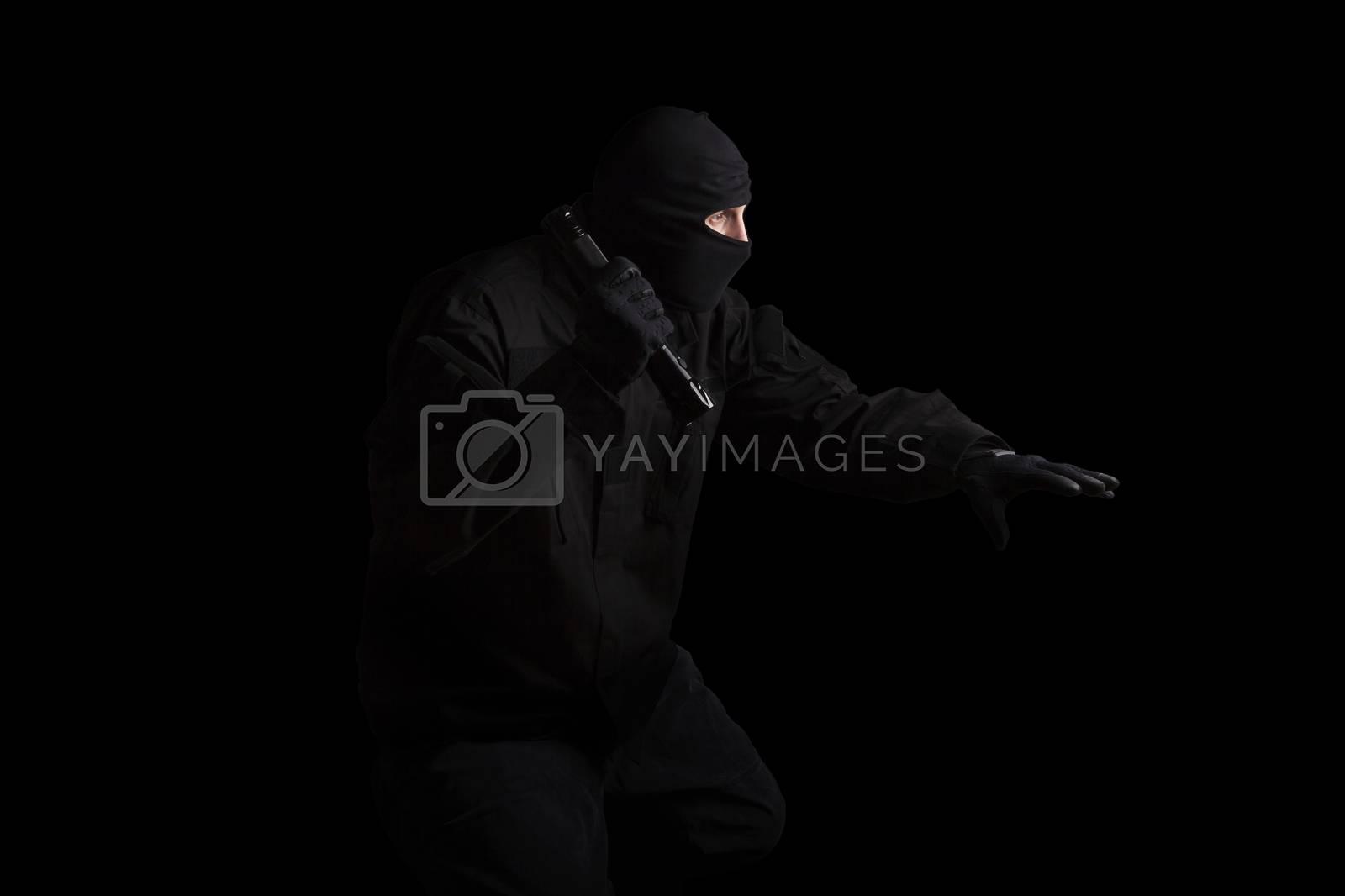 Man in black mask and black cloth holding flashlight isolated on black background. Dangerous criminal committing crime.
