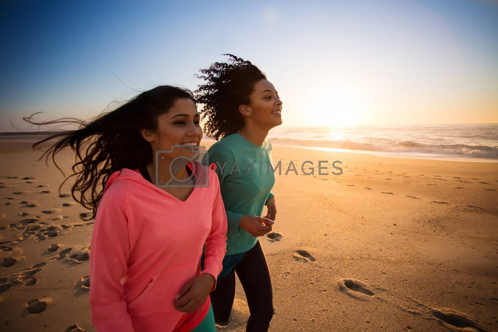 Couple of women running and walking on the beach