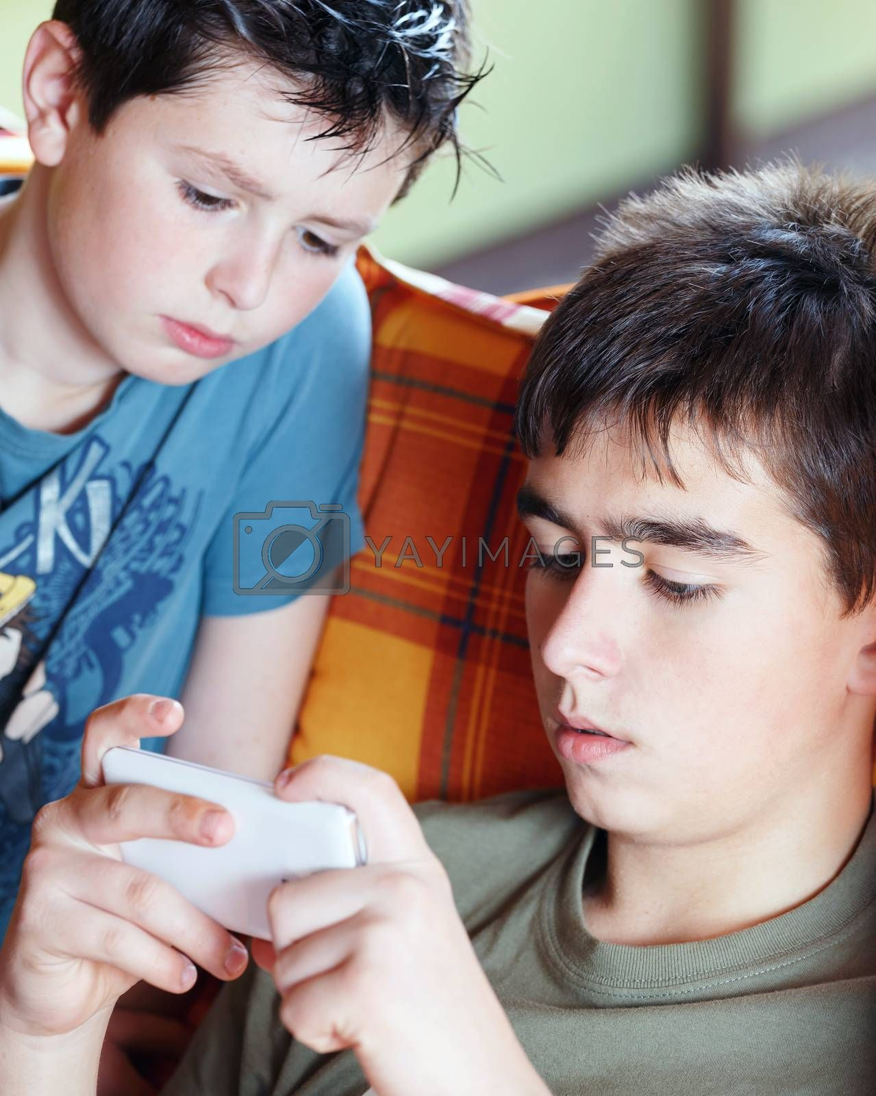 Royalty free image of Teenager boys playing on smartphone, outdoor by artush