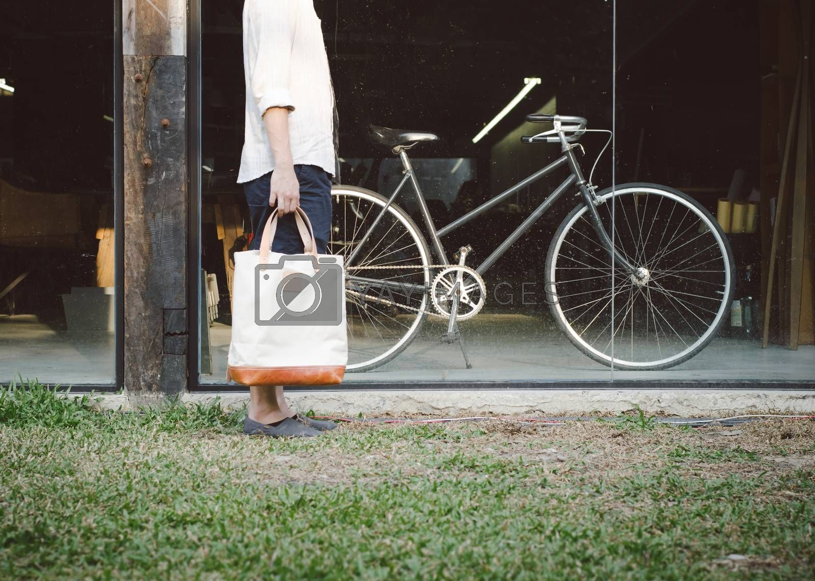 Royalty free image of Man with canvas bag and vintage bicycle on background by siraanamwong