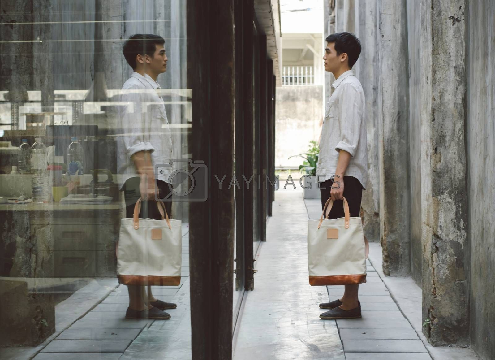 Royalty free image of Attractive man with canvas bag at grunge alleyway by siraanamwong