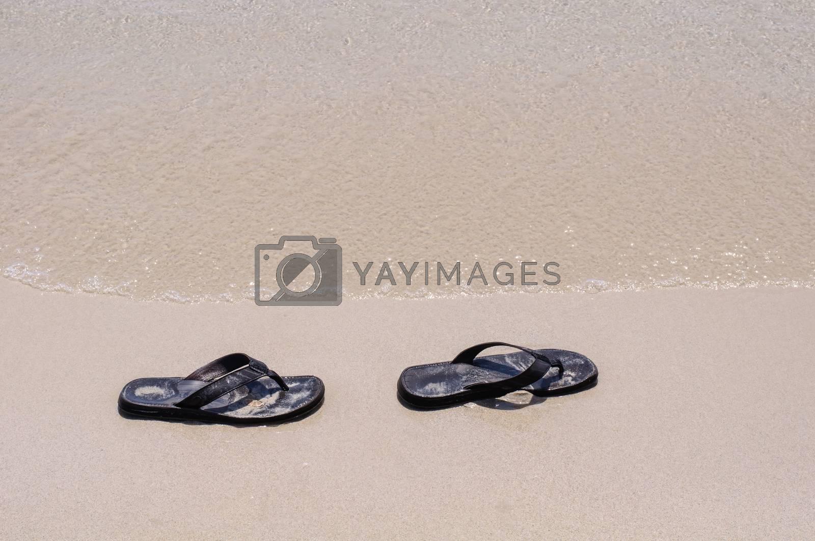 Royalty free image of Beach sandals on a sandy beach by Sorapop