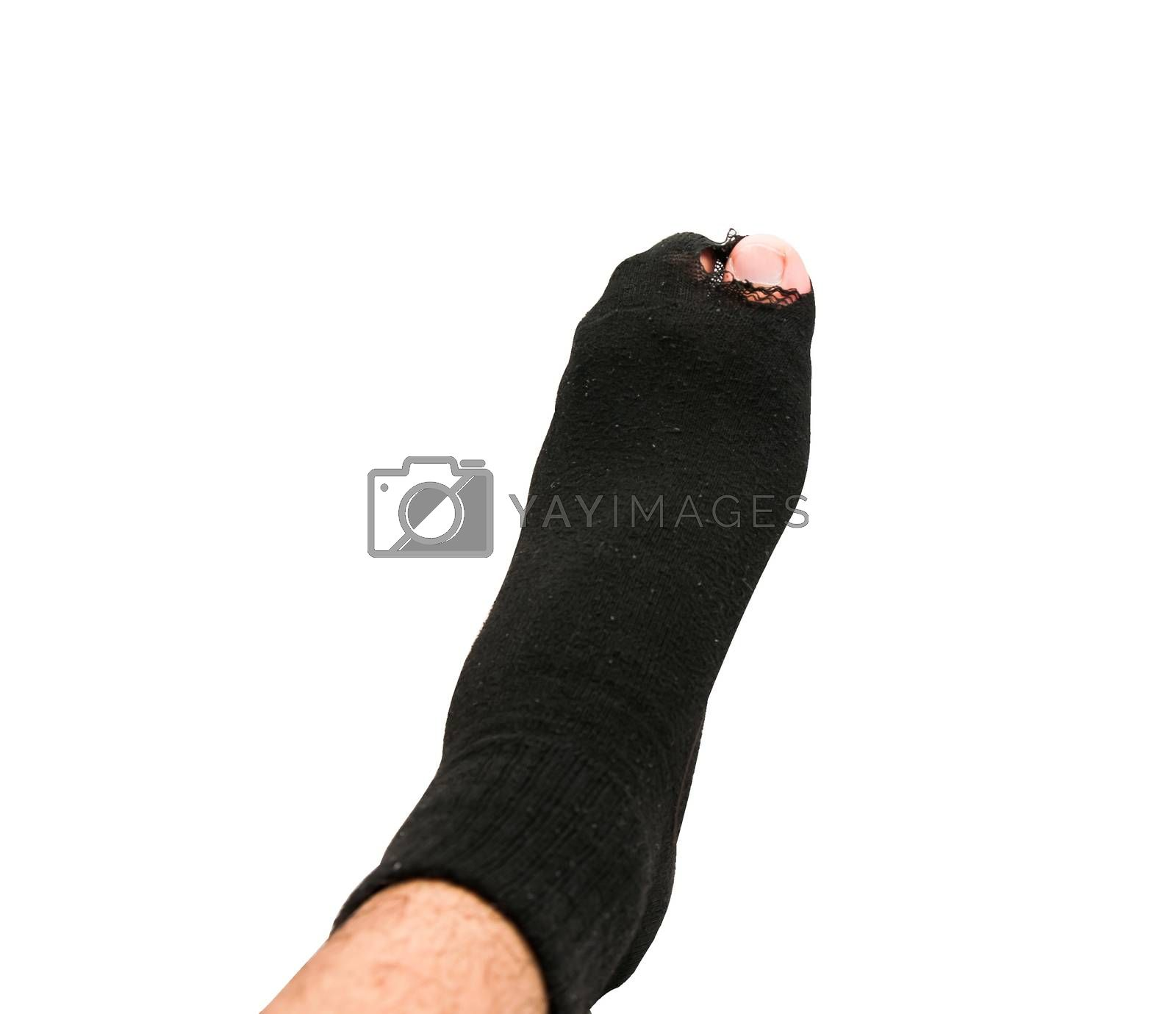 Royalty free image of Foot in old sock and torn by Sorapop