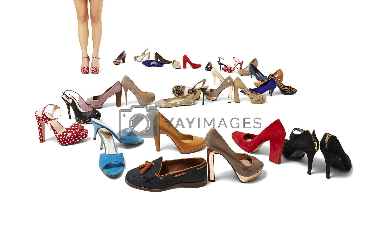 Royalty free image of Female legs and huge selection of shoes by filipw
