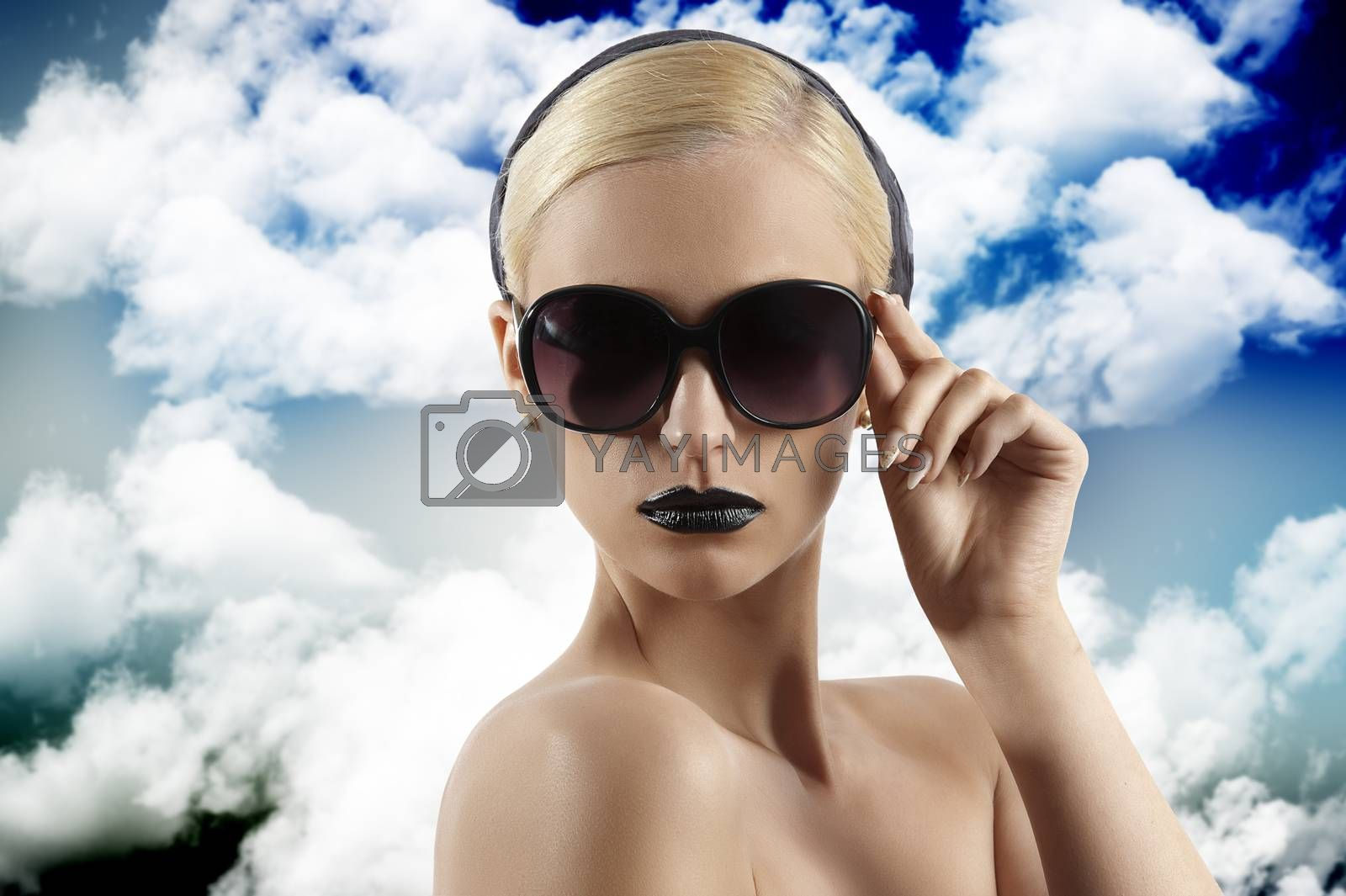 Royalty free image of fashion shot of blond girl with sunglasses looking at the camera by fotoCD