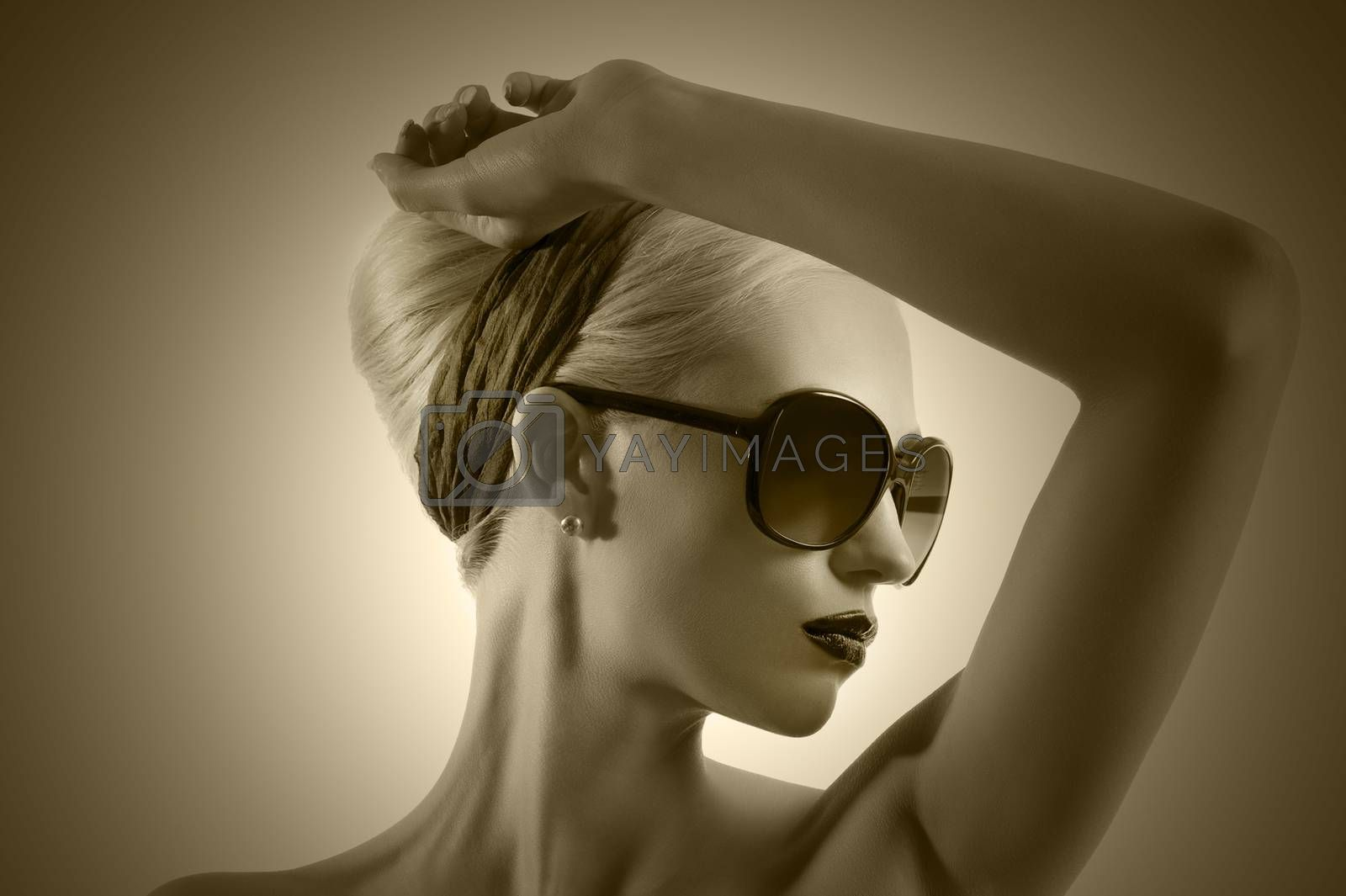 Royalty free image of fashion shot of blond girl with sunglasses posing against white  by fotoCD