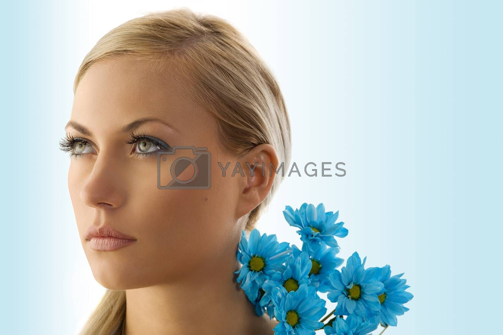 Royalty free image of blond girl with blue daisy by fotoCD