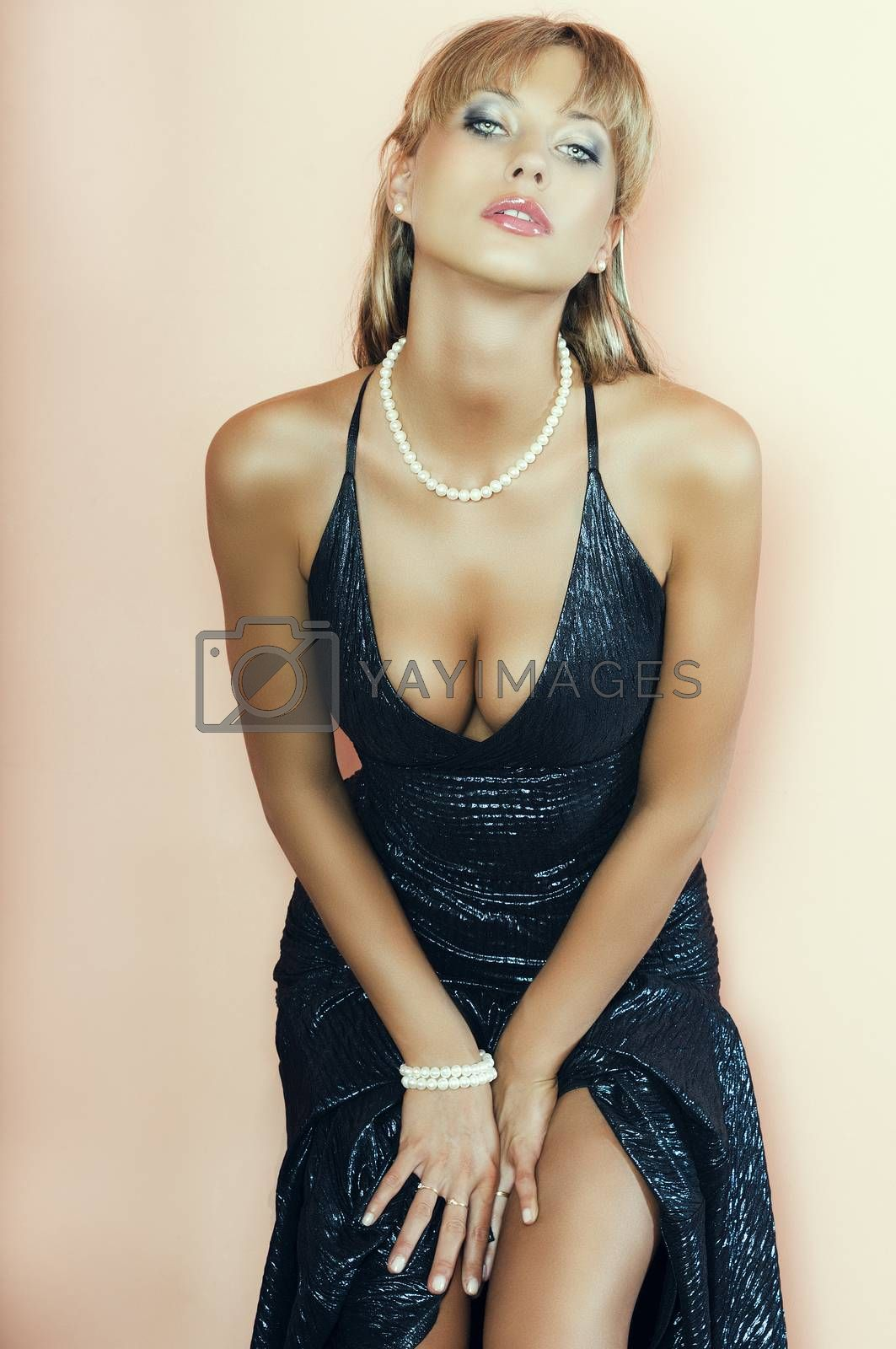 Royalty free image of pretty blonde girl with both hands on the legs by fotoCD