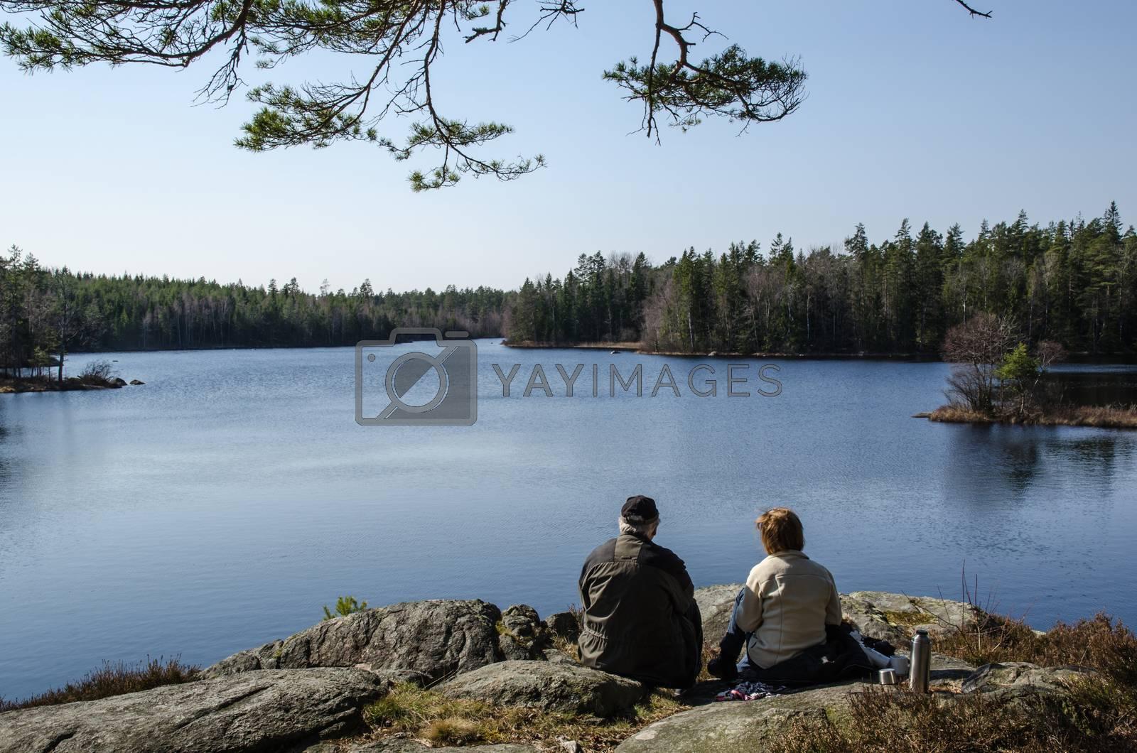 Royalty free image of Senior couple resting at lake side by olandsfokus