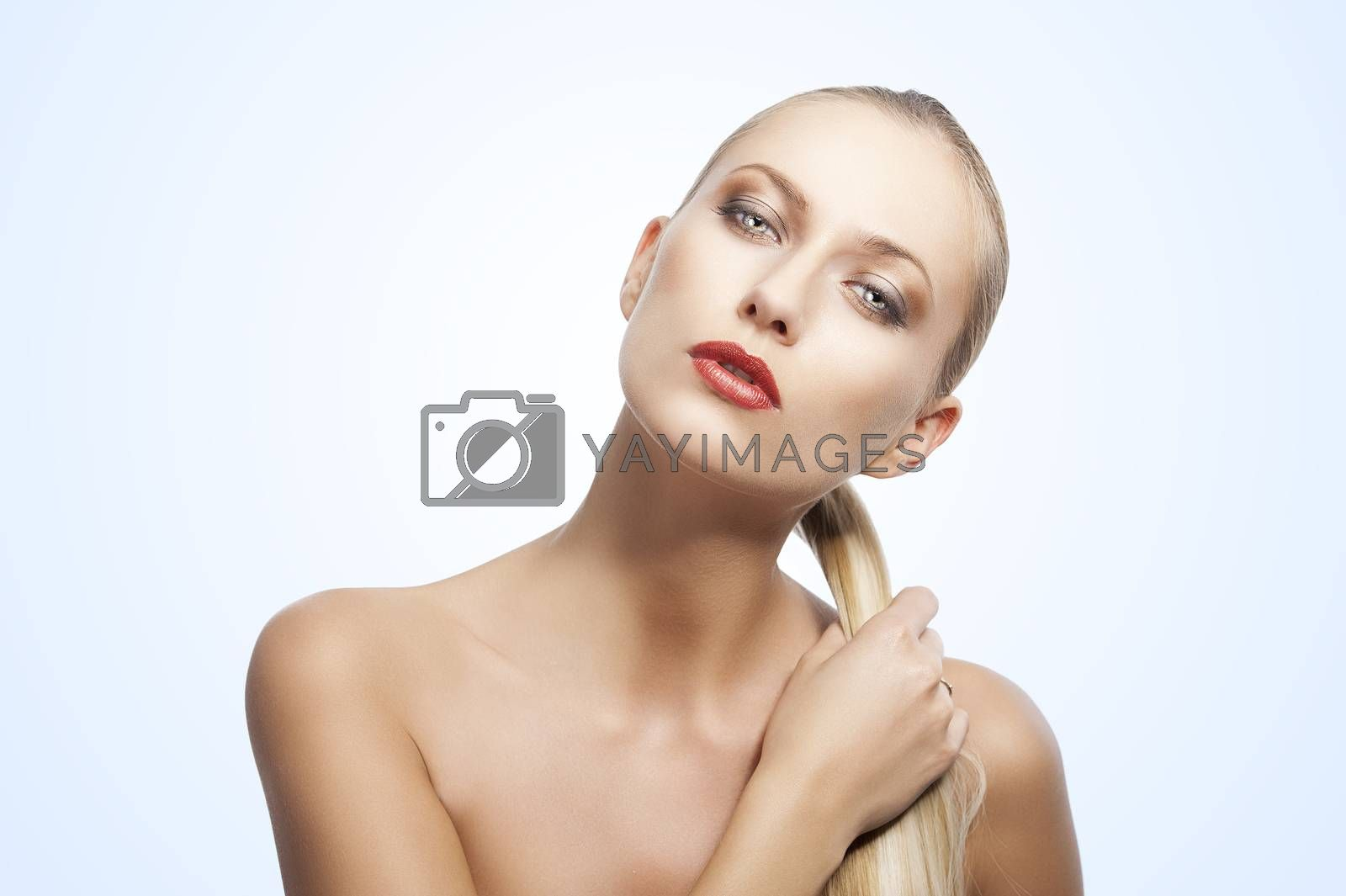 Royalty free image of beauty woman over white. She takes her tail of hair by fotoCD