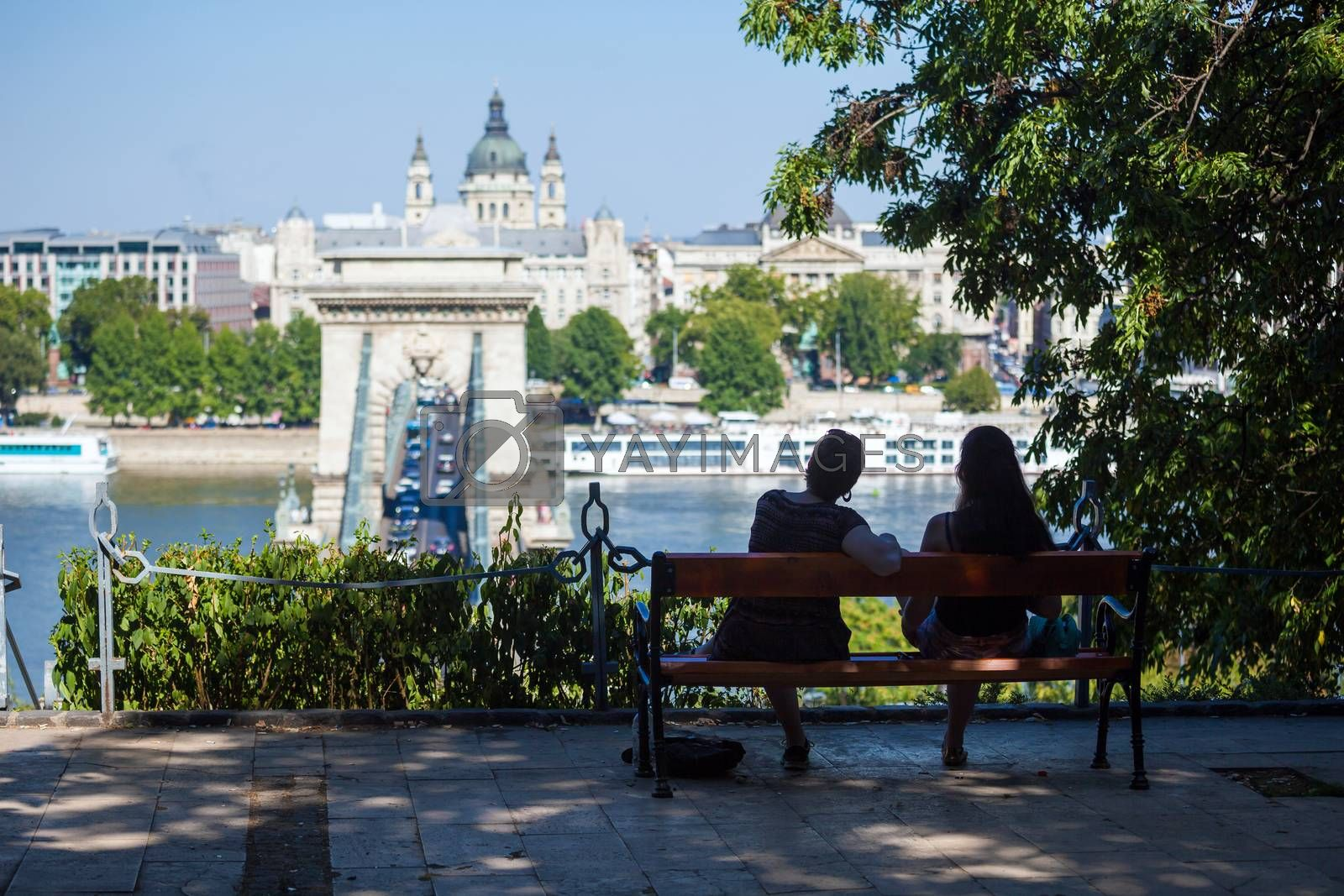 Royalty free image of  Two girls on a bench watching at Szechenyi Chain Bridge by PixAchi