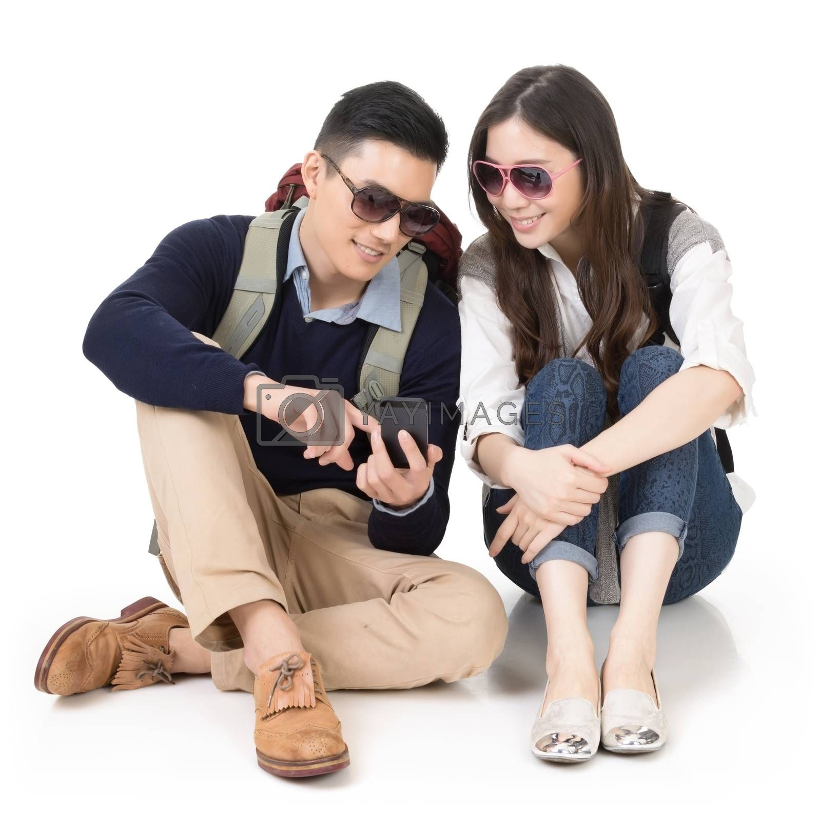 Royalty free image of Asian young couple traveling and using mobile phone by elwynn