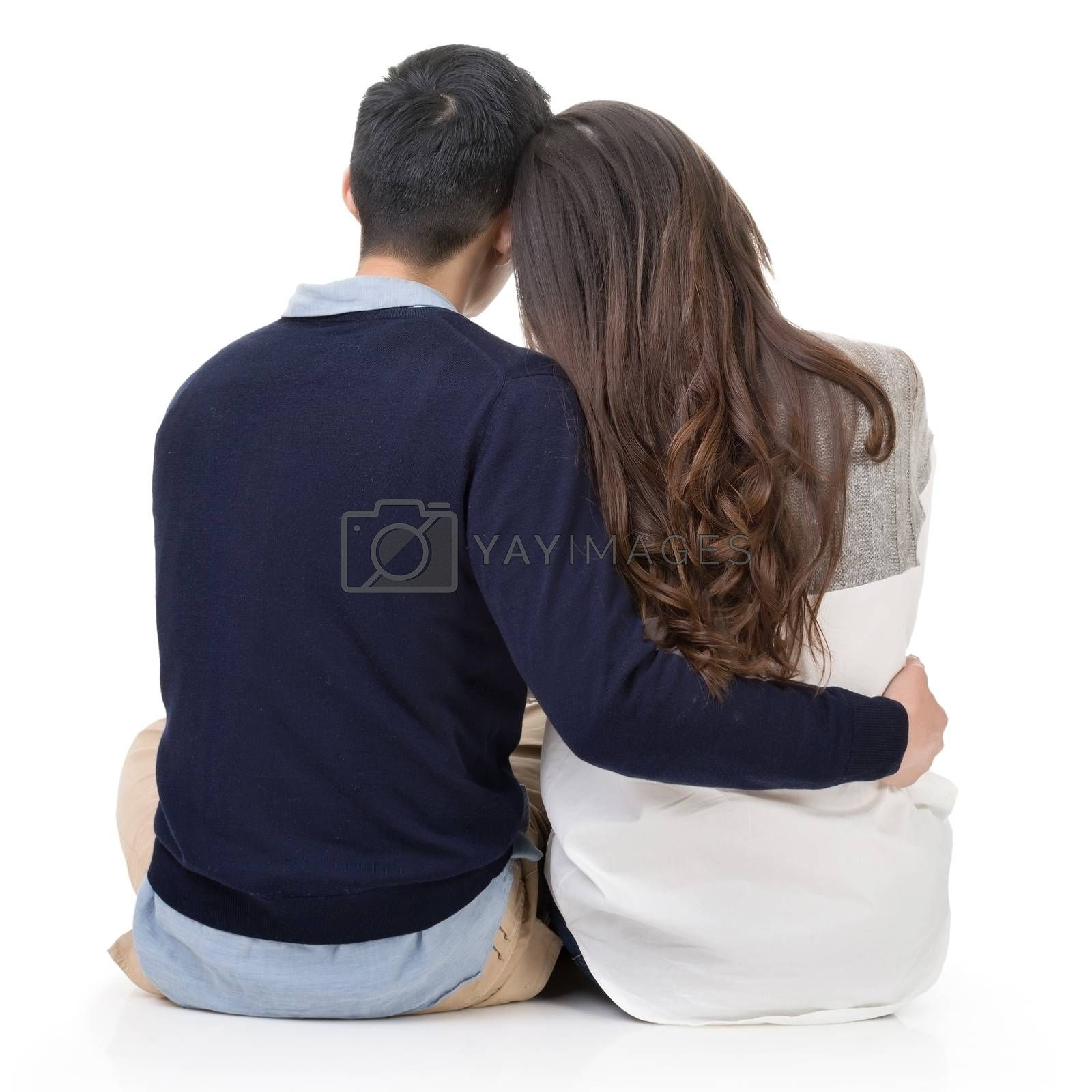 Royalty free image of Young couple sitting on ground and hugging by elwynn
