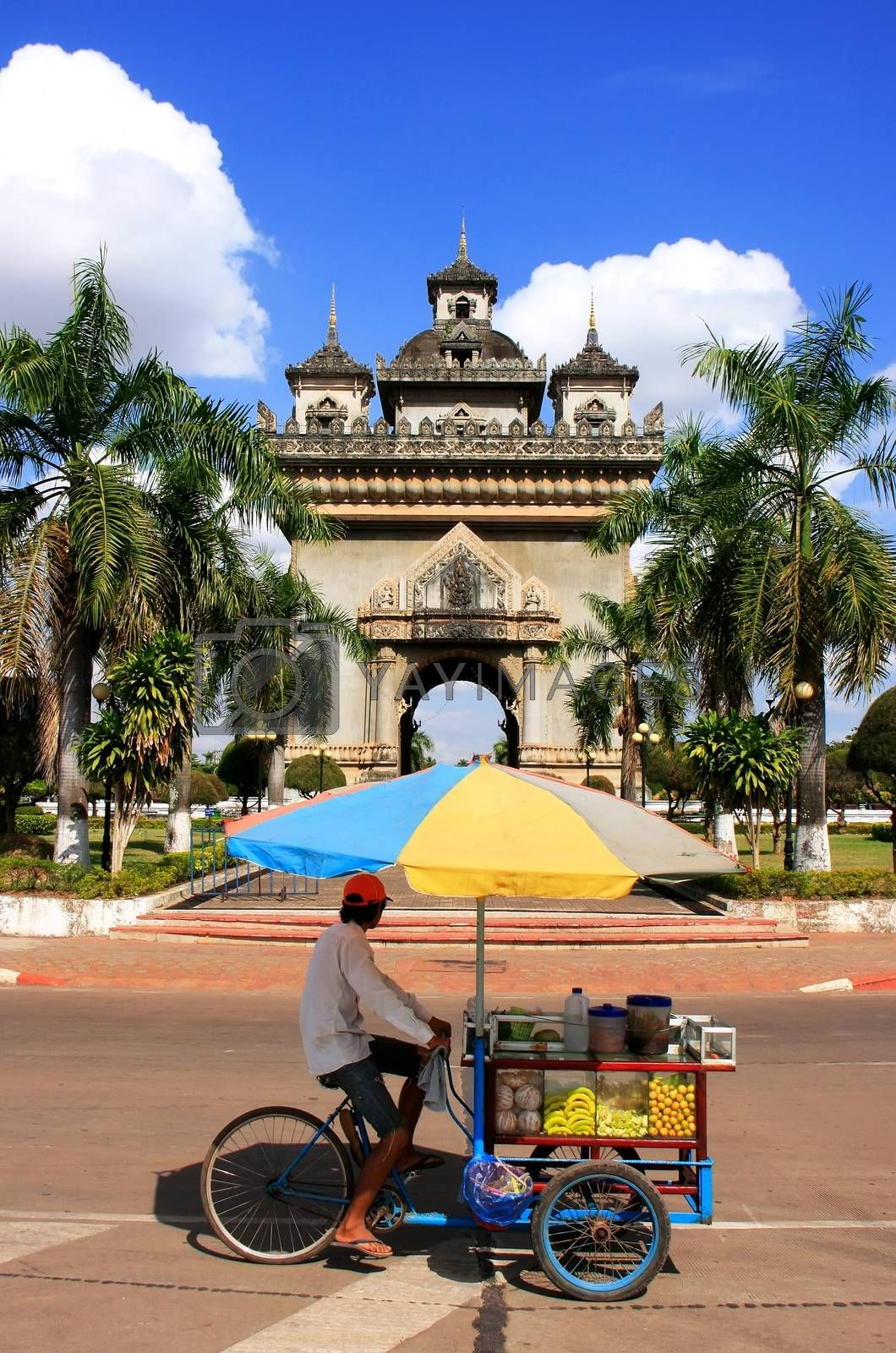 Royalty free image of Street food seller on a bicycle in front of Victory Gate Patuxai by donya_nedomam