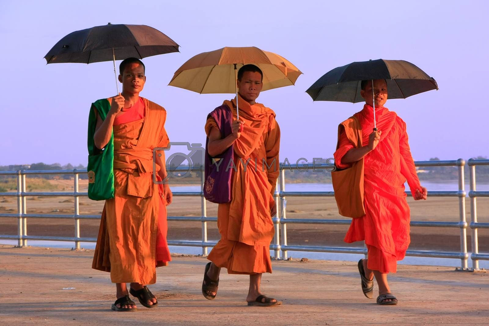 Royalty free image of Monks with umbrellas walking near Mekong river, Vientiane, Laos by donya_nedomam