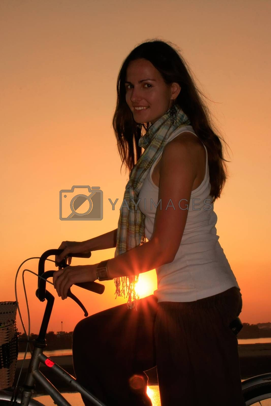 Royalty free image of Silhouetted woman with bicycle at Mekong river waterfront at sun by donya_nedomam