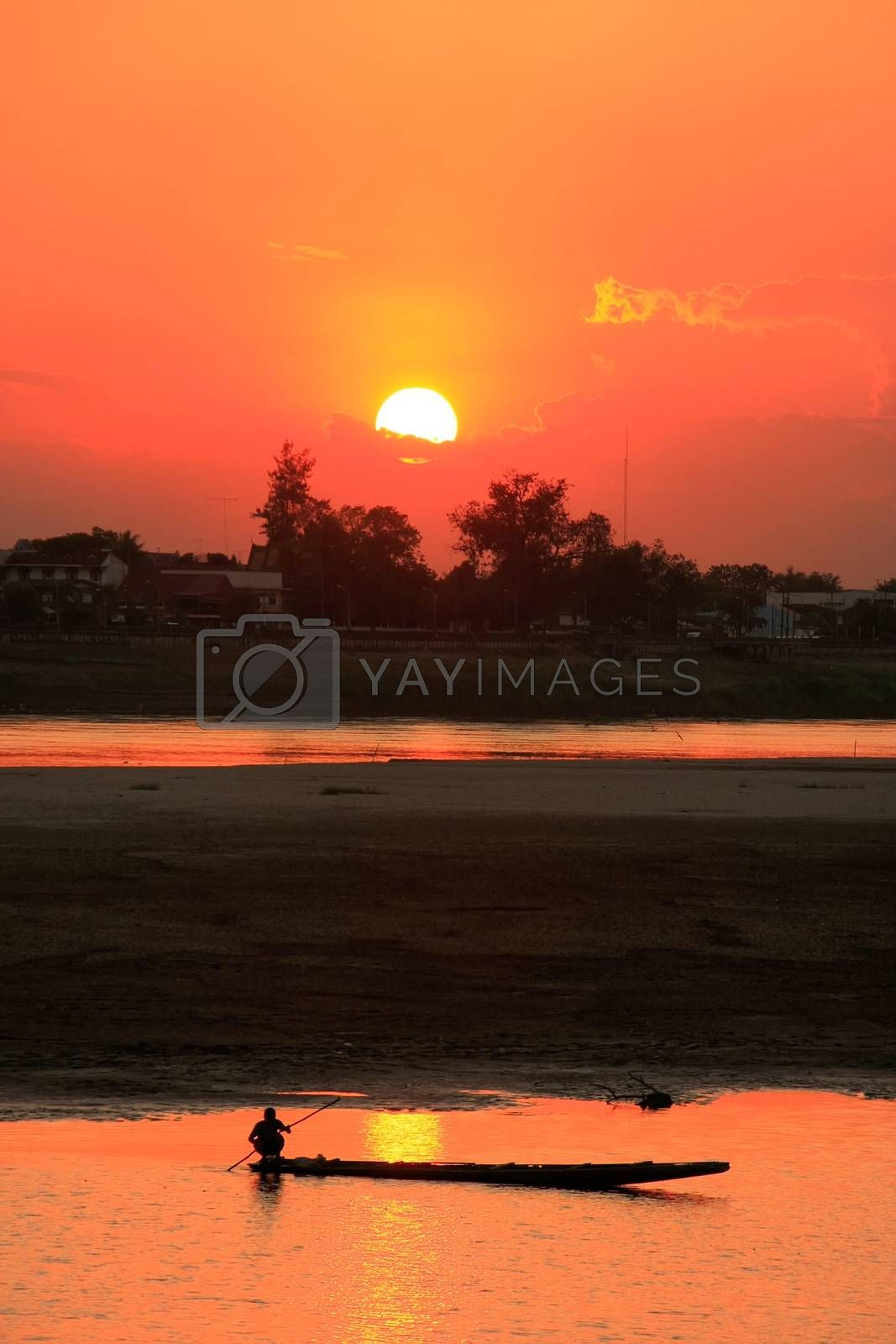 Royalty free image of Silhouetted boat on Mekong river at sunset, Vientiane, Laos by donya_nedomam