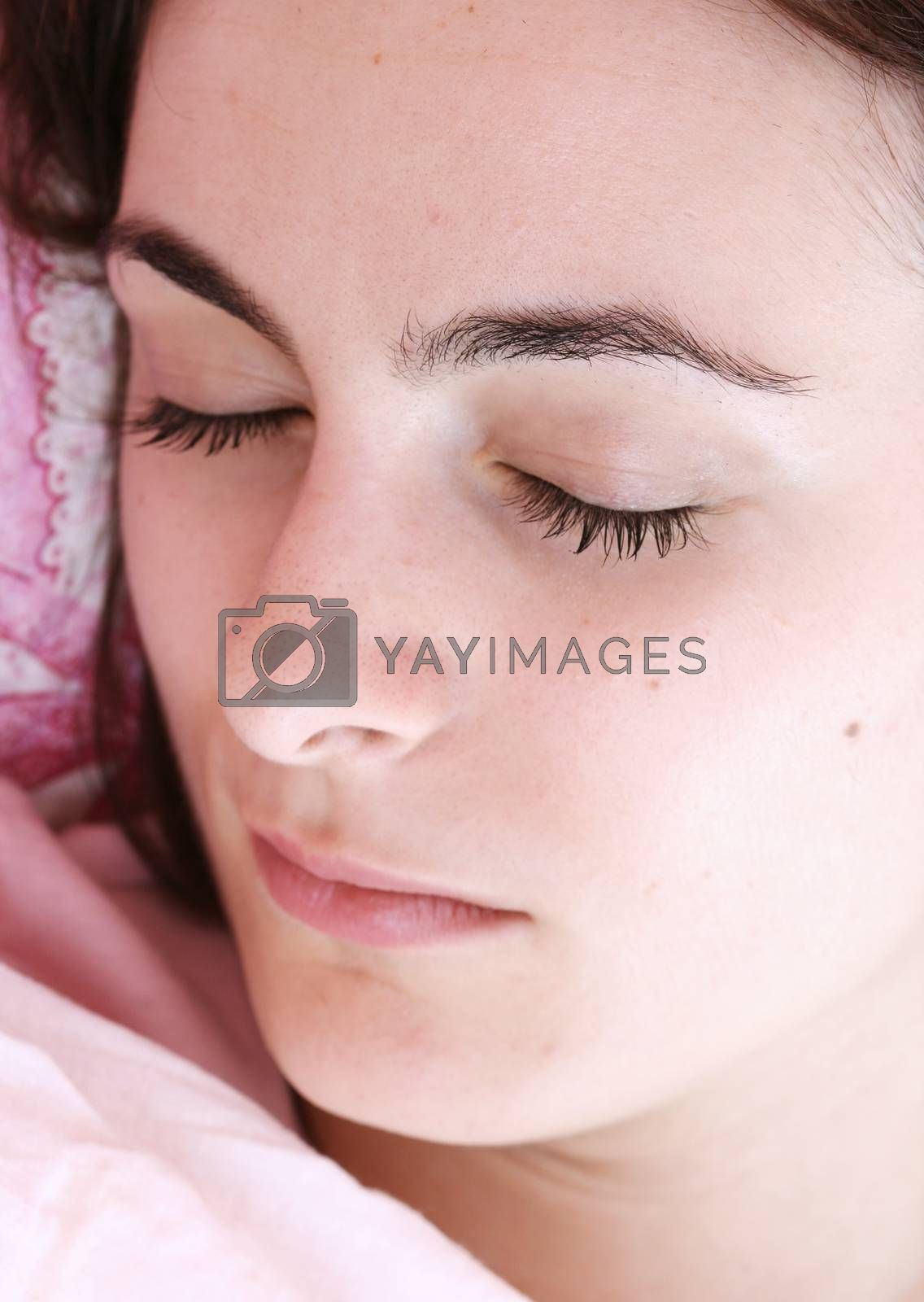 Beautiful young woman sleeping on bed in her bedroom at home in the morning.